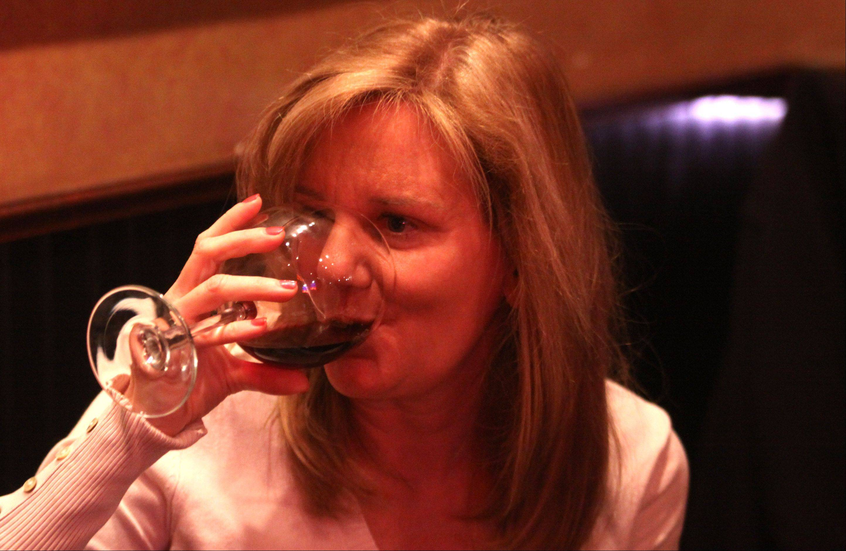 Vickie Reilly, of Arlington Heights, sips a glass of wine at the Tuscan Market Wine Bar in Arlington Heights.