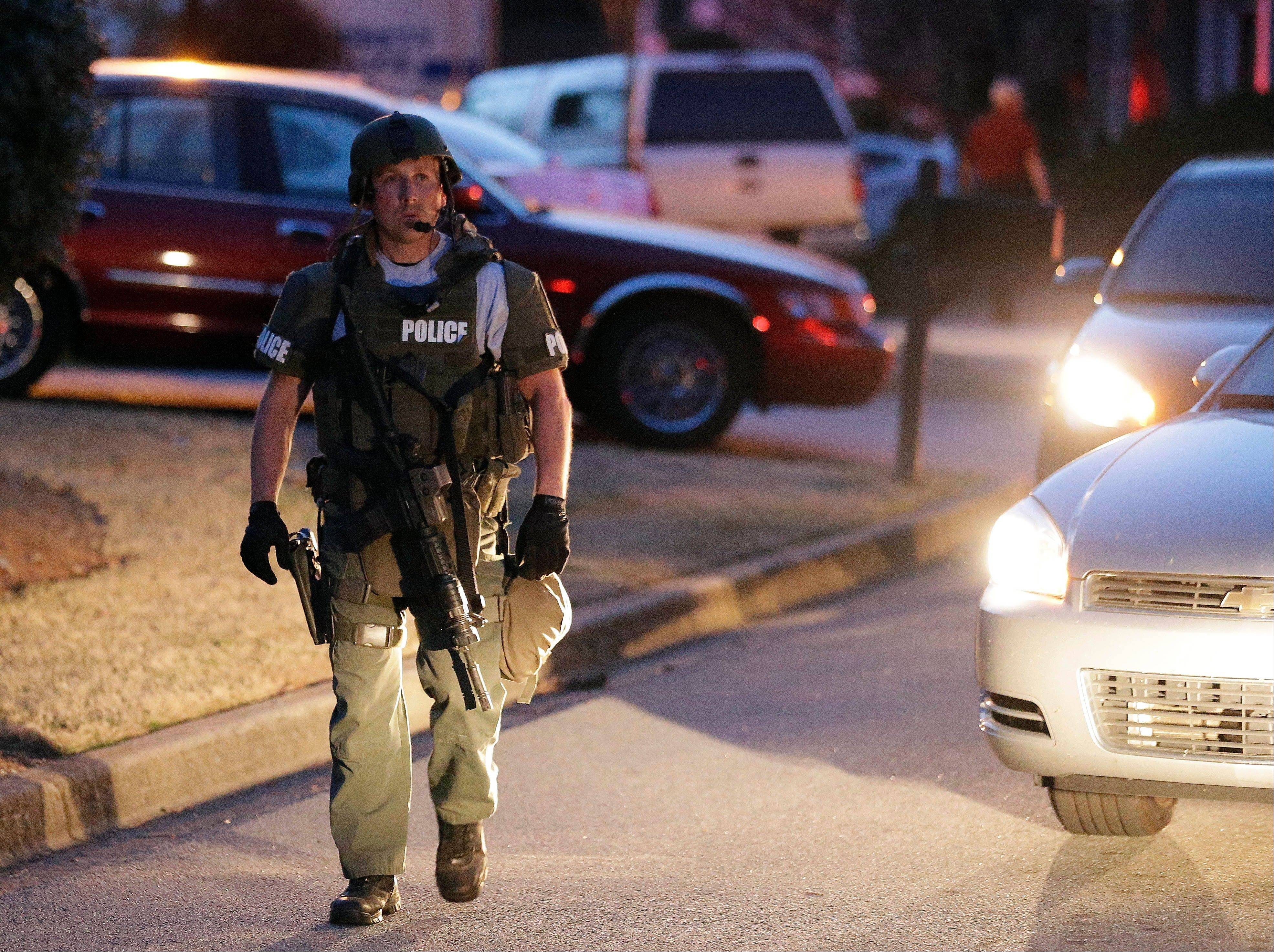 A police officer leaves the scene after an explosion and gunshots were heard near the scene where a man was holding four firefighters hostage Wednesday in Suwanee, Ga. A police spokesman said the suspect was dead and none of the hostage suffered serious injuries.