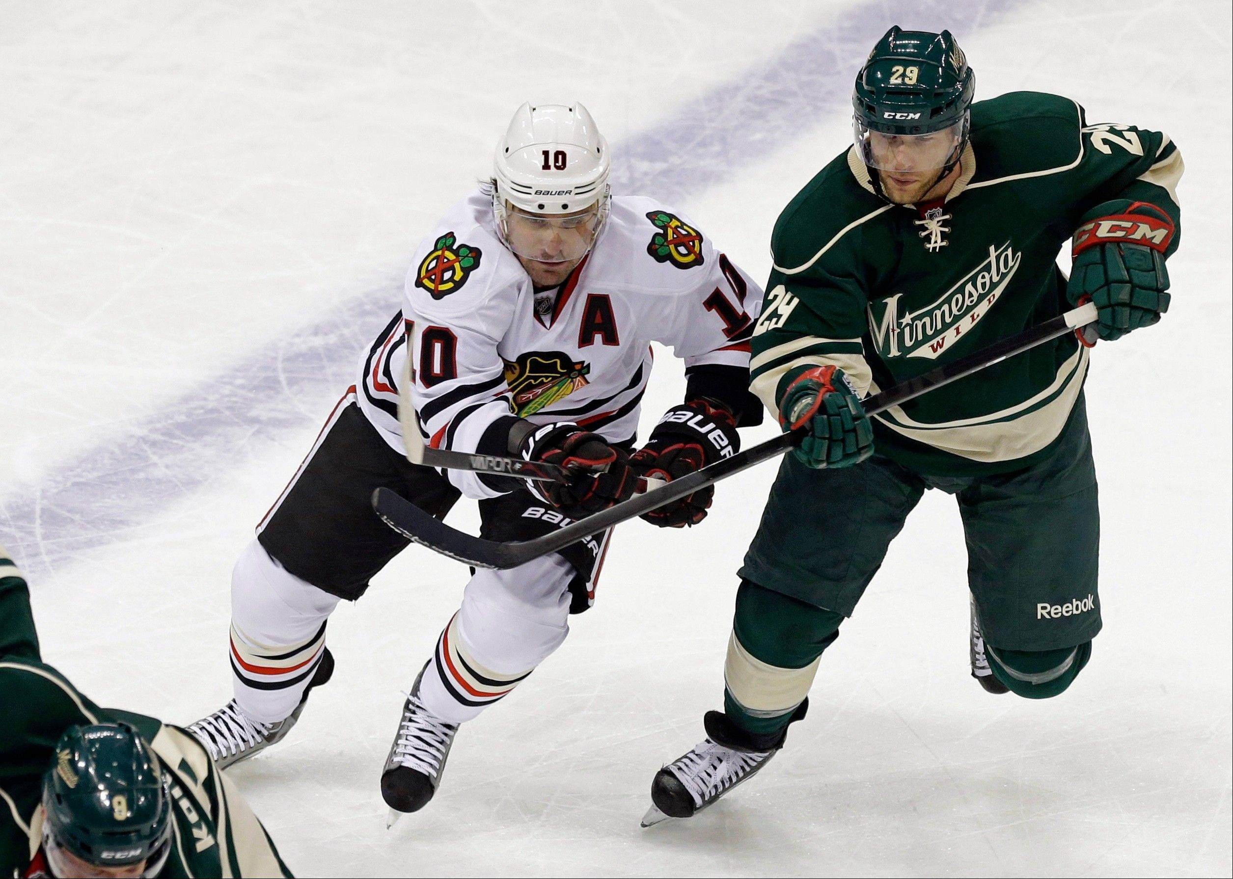 Chicago Blackhawks' Patrick Sharp, left, making his return to the ice, and new Minnesota Wild player Jason Pominville, chase the puck in the first period of an NHL hockey game Tuesday, April 9, 2013 in St. Paul. Sharp has returned to the Chicago Blackhawks' lineup after a 14-game absence because of a shoulder injury.