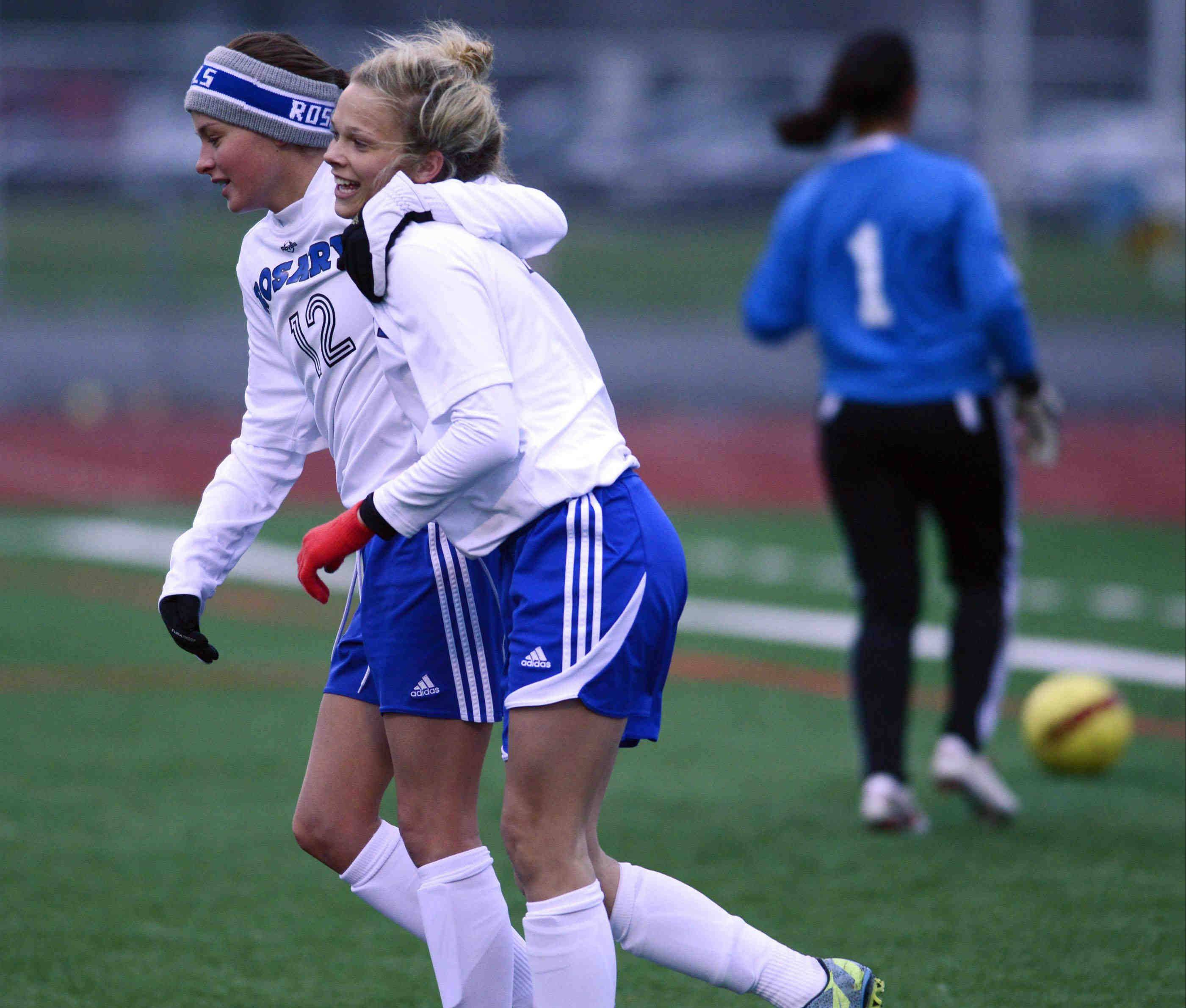Rosary's Kaitlin Johnson hugs teammate Quincy Kellett after Kellet's first goal against West Aurora Wednesday in Aurora. They both scored in the first half of the Royals' 6-2 victory.