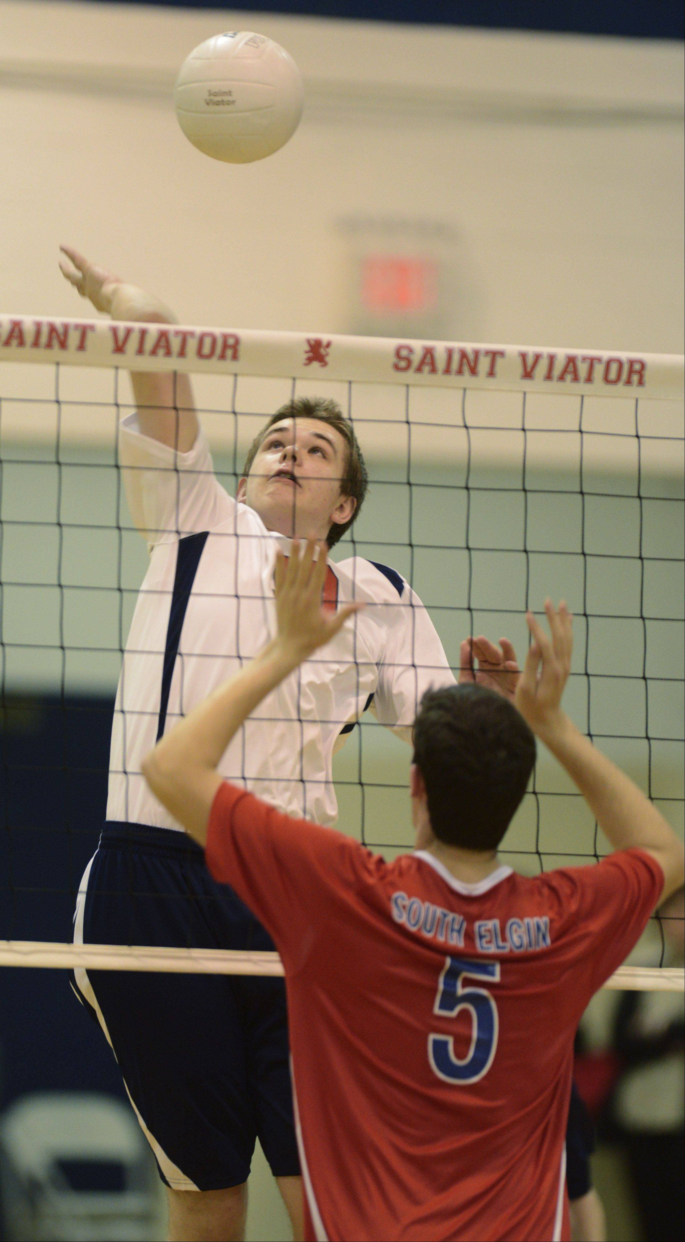 St. Viator's Matt Szleszynski leaps for a kill as South Elgin's Dan Gibadlo stands ready at the net during Wednesday's game in Arlington Heights.