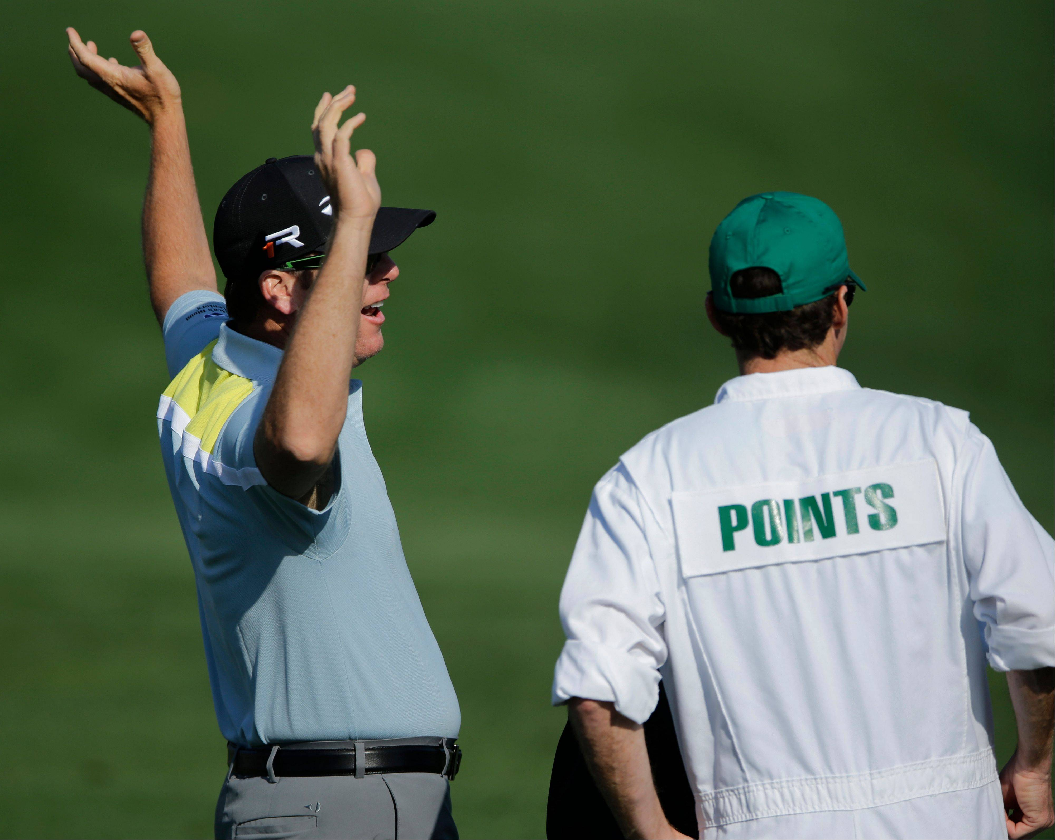 D.A. Points stretches while speaking with his caddie Travis Perkins on the driving range during a practice round for the Masters in Augusta, Ga. Points is making his second appearance in the Masters.