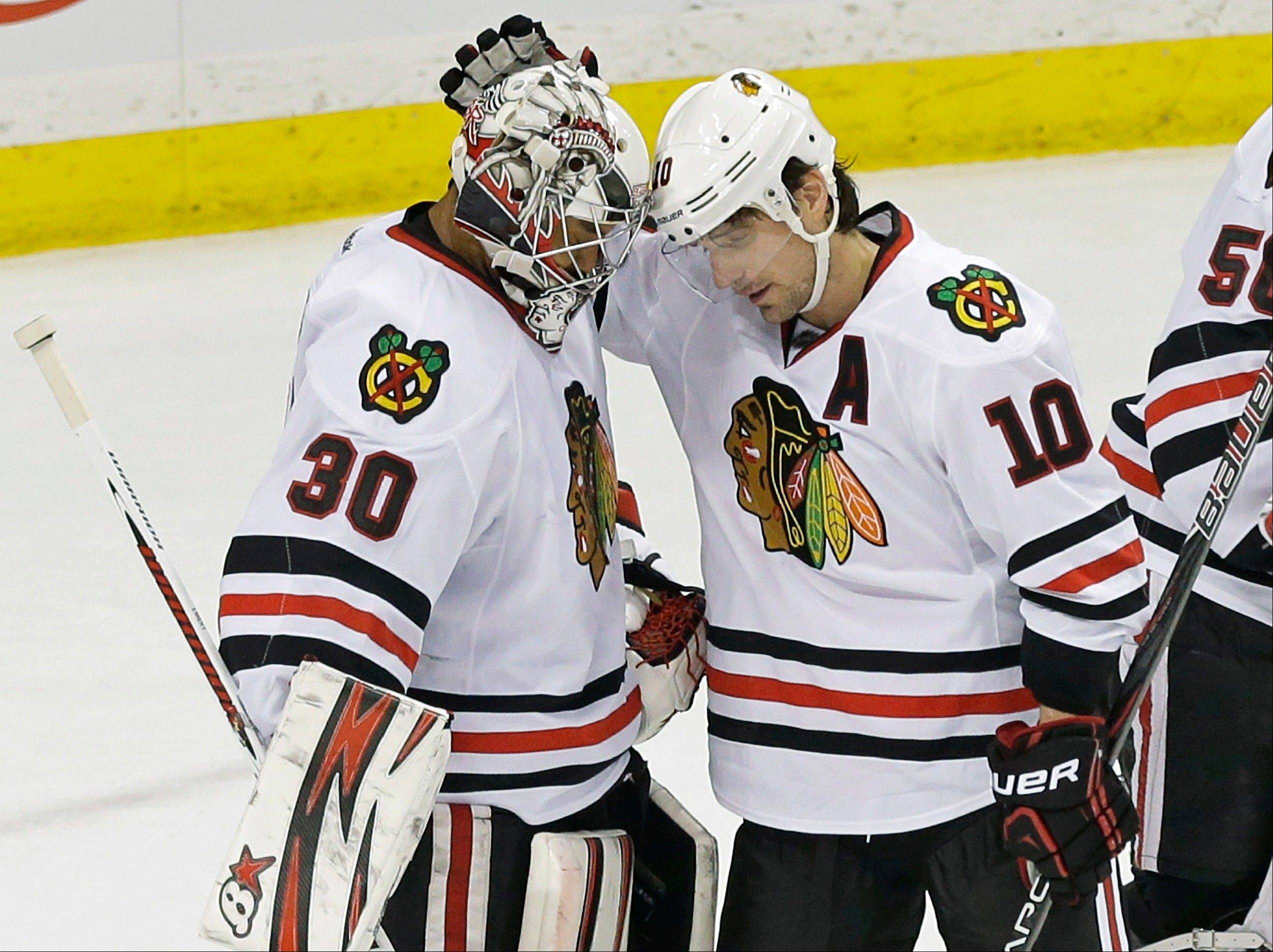 Chicago Blackhawks' Patrick Sharp, right, congratulates goalie Ray Emery after he shut out the Minnesota Wild in a 1-0 victory in an NHL hockey game Tuesday, April 9, 2013 in St. Paul.