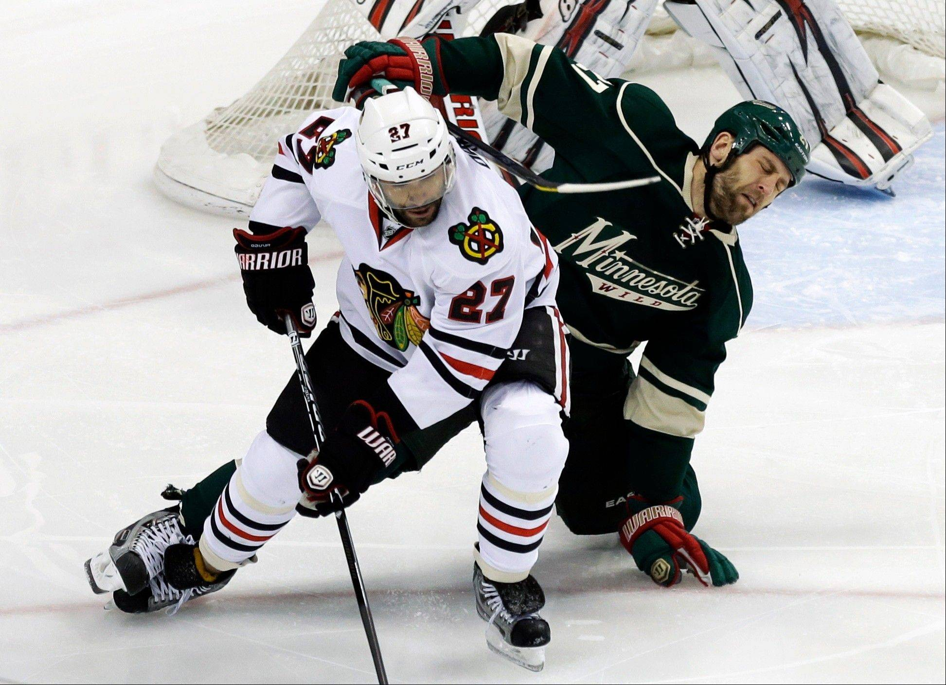 Chicago Blackhawks' Johnny Oduya, left, of Sweden, and Minnesota Wild's Mike Rupp get tangled up in a race for the puck in the first period of an NHL hockey game Tuesday, April 9, 2013 in St. Paul.