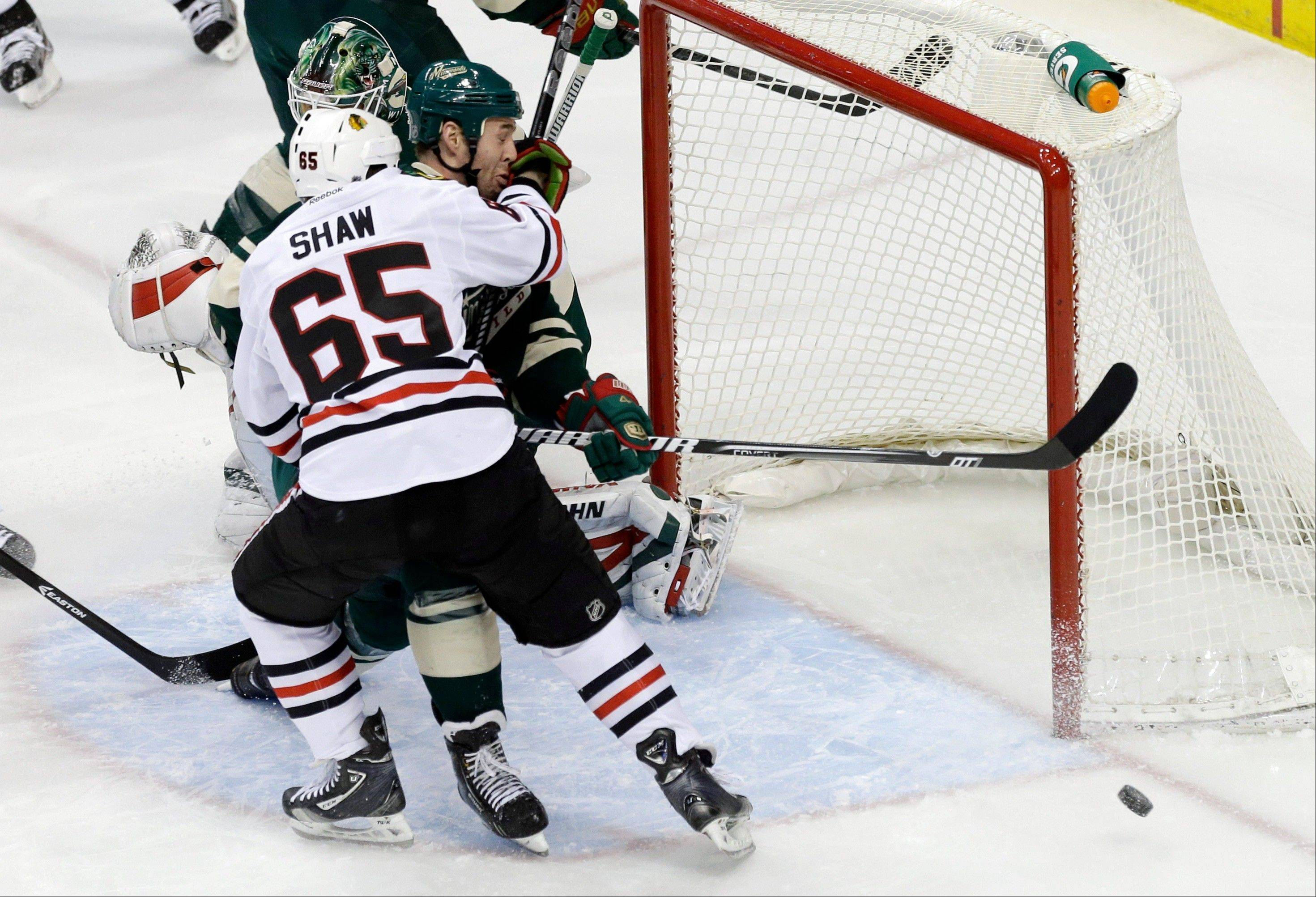 Chicago Blackhawks' Andrew Shaw keeps Minnesota Wild's Clayton Stoner from chasing the puck in his own end in the first period of an NHL hockey game Tuesday, April 9, 2013 in St. Paul.