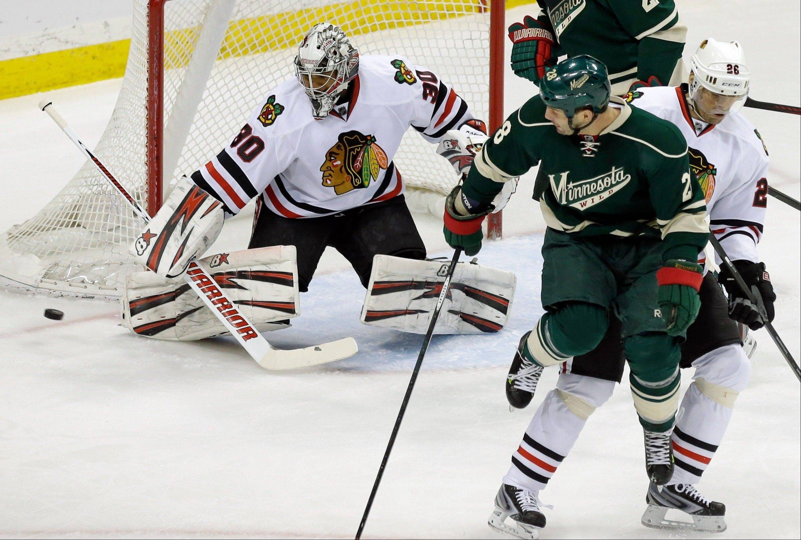Minnesota Wild's Zenon Konopka, second from right, jumps to make way for a shot which went wide of Chicago Blackhawks goalie Ray Emery in the first period of an NHL hockey game Tuesday, April 9, 2013 in St. Paul.At right is Blackhawks' Michael Handzus.