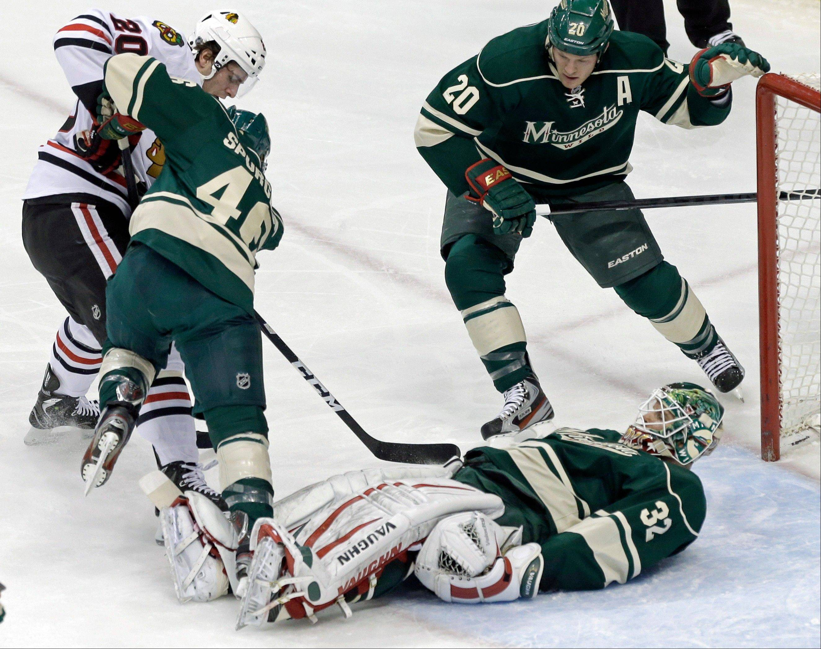 MinnesostaWild's Jared Spurgeon 46) tries to keep Chicago Blackhawks' Brandon Saad, left, away from the puck and fallen Wild goalie Niklas Backstrom of Finland in the first period of an NHL hockey game Tuesday, April 9, 2013 in St. Paul.