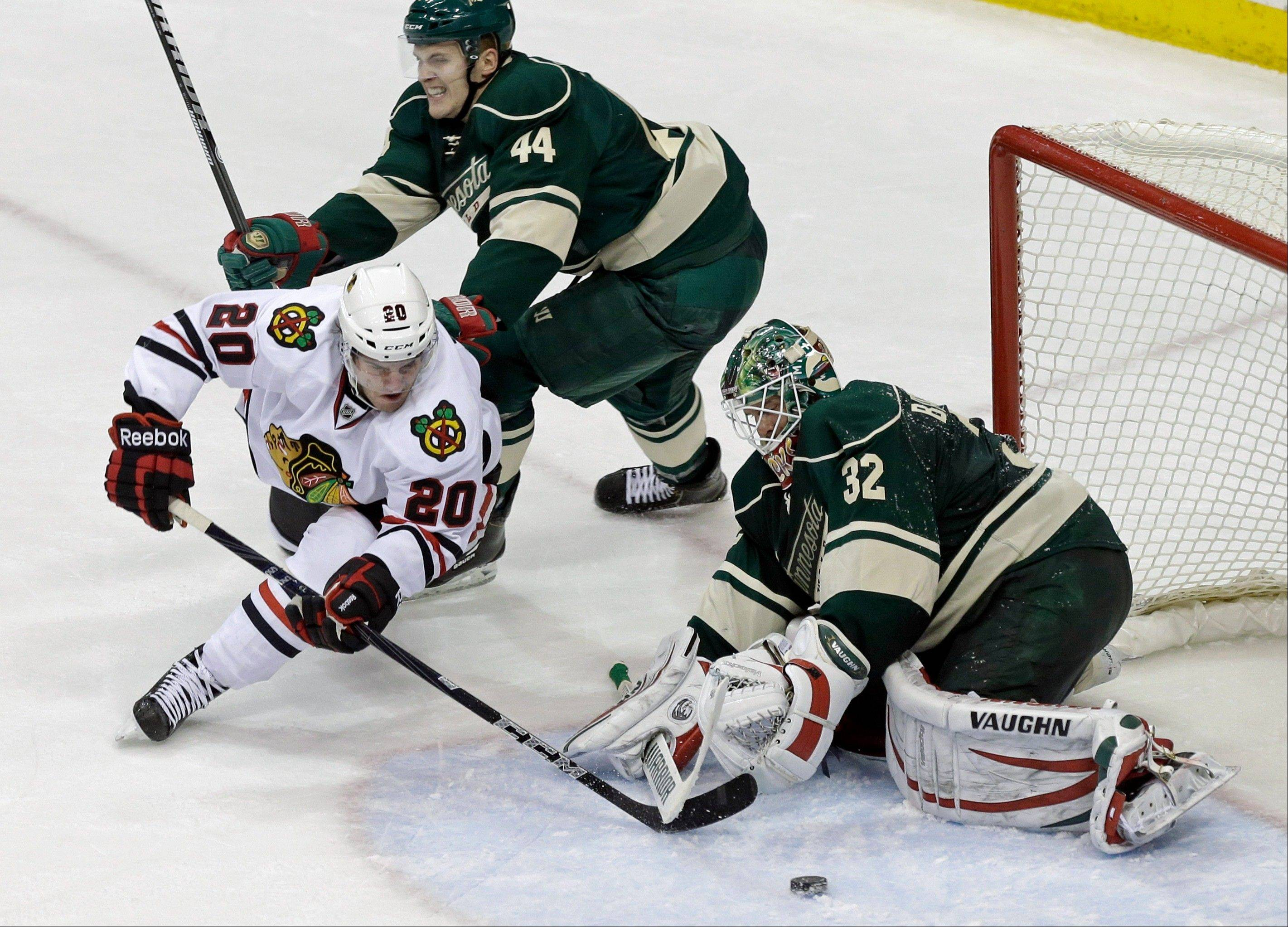 A shot attempt by Chicago Blackhawks' Brandon Saad, left, goes wide of Minnesota Wild goalie Niklas Backstrom of Finland in the third period of an NHL hockey game Tuesday, April 9, 2013 in St. Paul. The Blackhawks won 1-0. Defending is Wild's Justin Falk, top.
