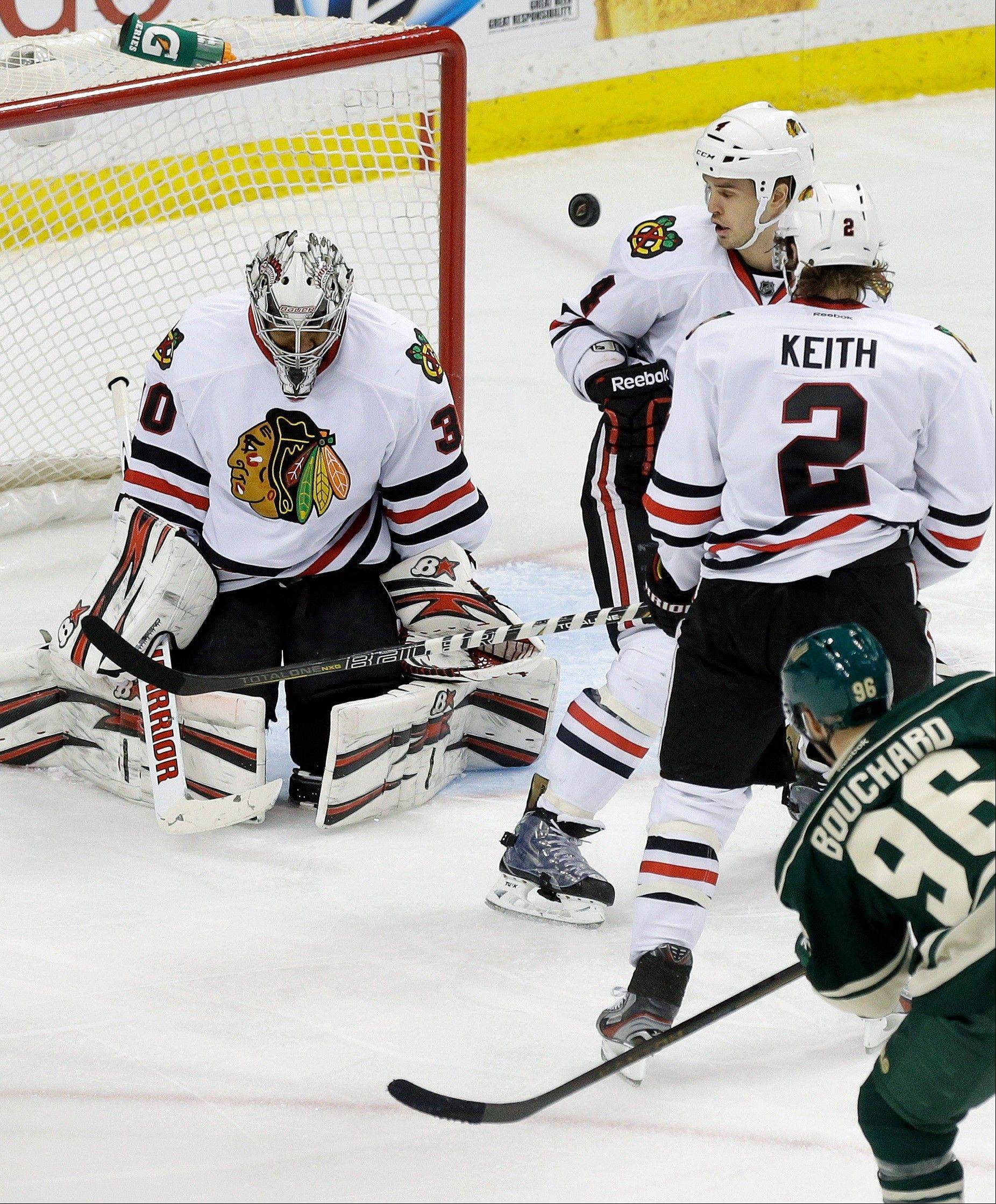 Chicago Blackhawks goalie Ray Emery, left, deflects a shot by Minnesota Wild's Pierre-Marc Bouchard, right, as Blackhawks' Duncan Keith (2) and Niklas Hjalmarsson of Sweden watch in the third period of an NHL hockey game Tuesday, April 9, 2013 in St. Paul. The Blackhawks won 1-0.