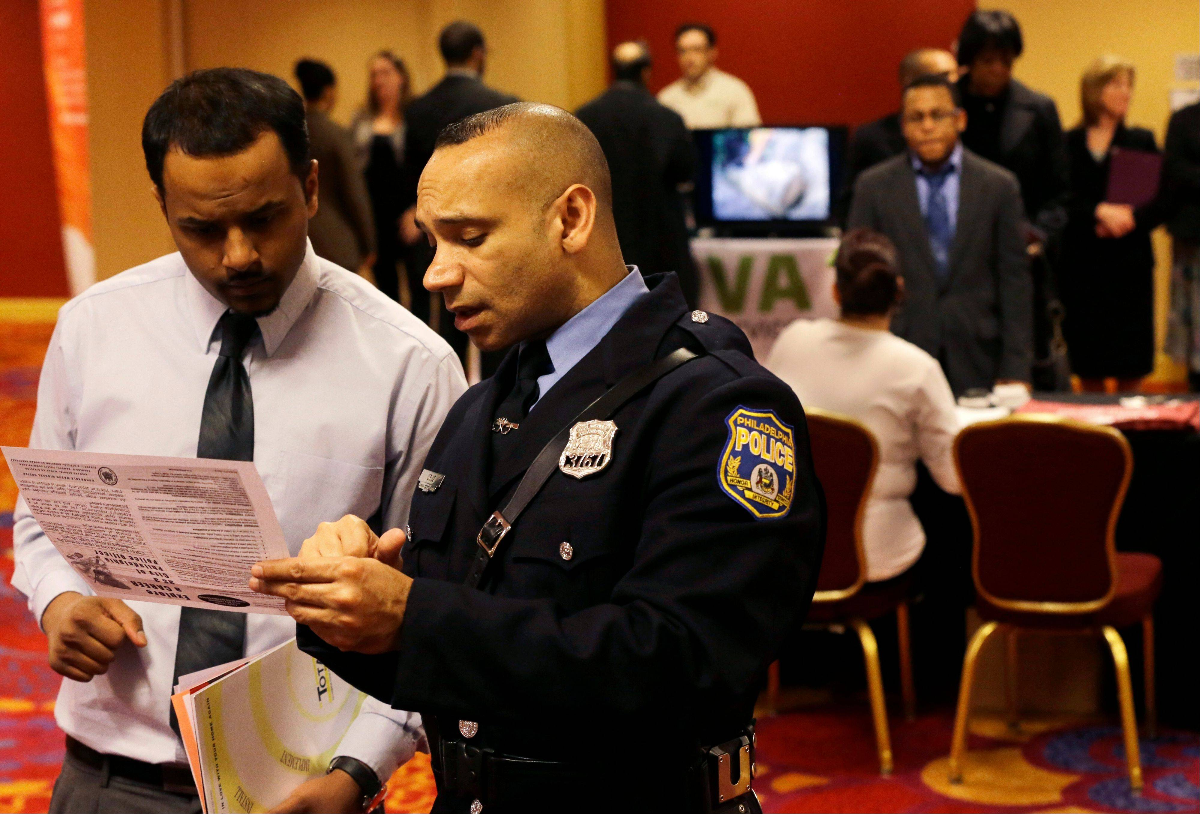 Philadelphia police recruiting officer Samuel Cruz, right, talks with Ismail Azeer of Carteret, N.J., at the Edison Career Fair job fair in the Iselin section of Woodbridge Township, N.J.