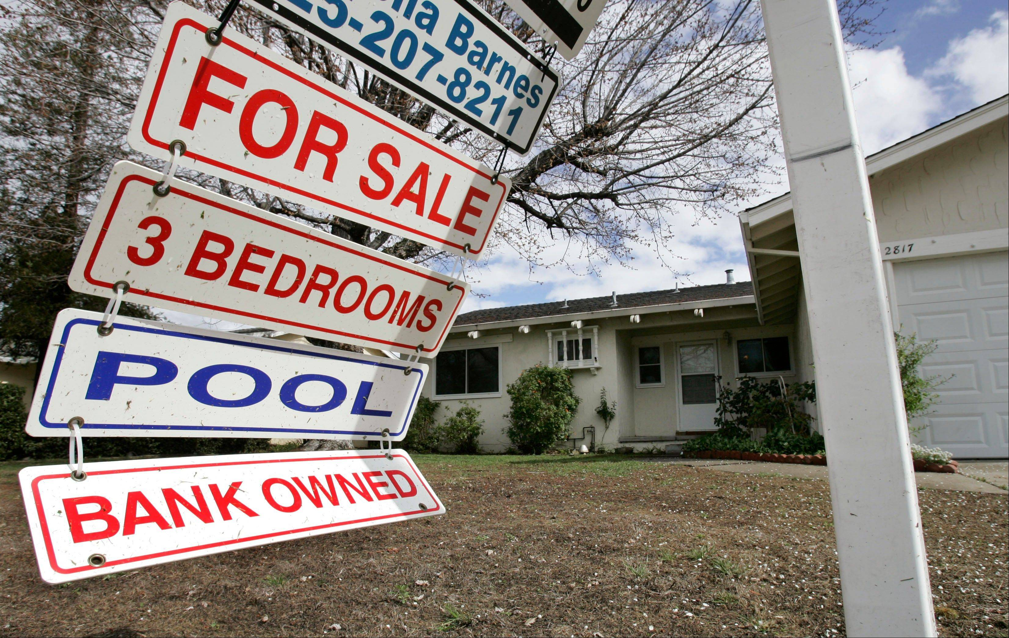 A foreclosure sign blows in the wind in front of a home under foreclosure in Antioch, Calif.