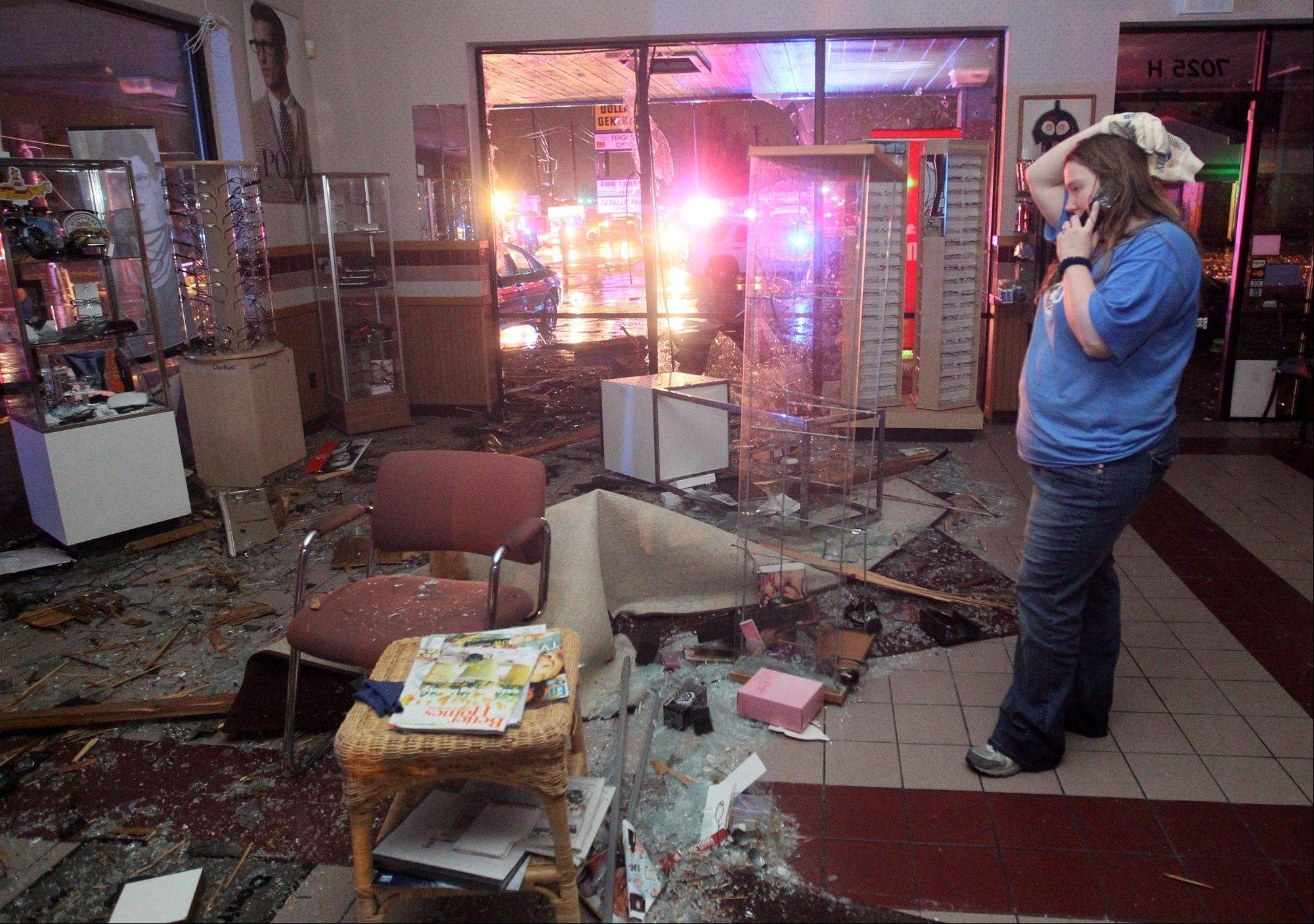 Kristin Little, manager of the Ferguson Optical shop in Hazelwood, talks with a friend on the phone as she describes the damage caused to her shop by a storm on Wednesday, April 10, 2013. Butch Dye, a hydrometeorological technician with the National Weather Service in St. Louis, Mo., said severe weather struck the suburb of Hazelwood. �We won�t be able to confirm whether it was a tornado until teams get out there tomorrow,� Dye said.