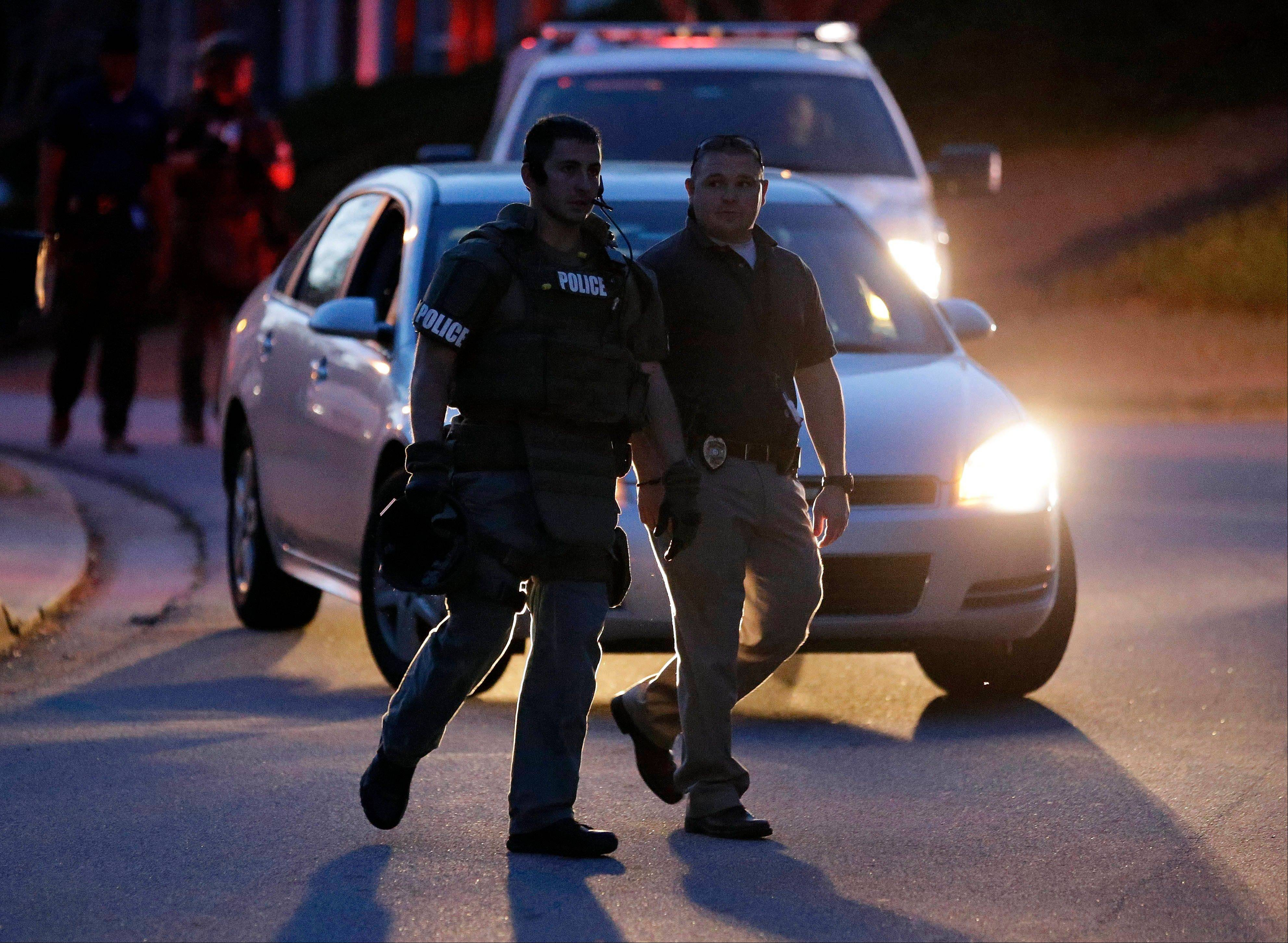 A police officer leaves the scene after an explosion and gunshots were heard near the scene where a man was holding four firefighters hostage Wednesday, April 10, 2013 in Suwanee, Ga. A police spokesman said the suspect was dead and none of the hostage suffered serious injuries.