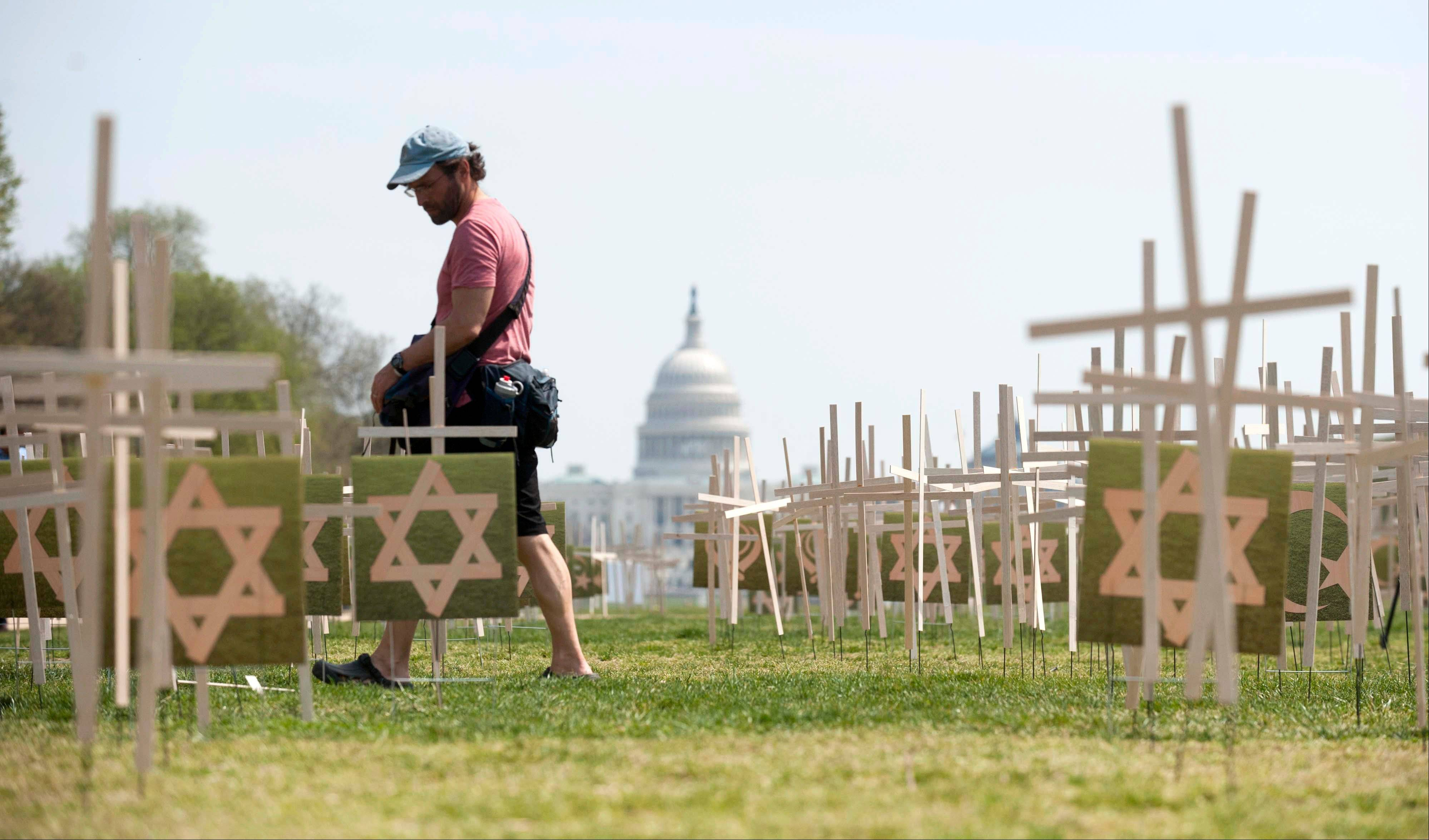With the Capitol in the background, a man walks past thousands of grave markers erected in a mock cemetery on the National Mall in Washington Thursday to honor victims of gun violence.