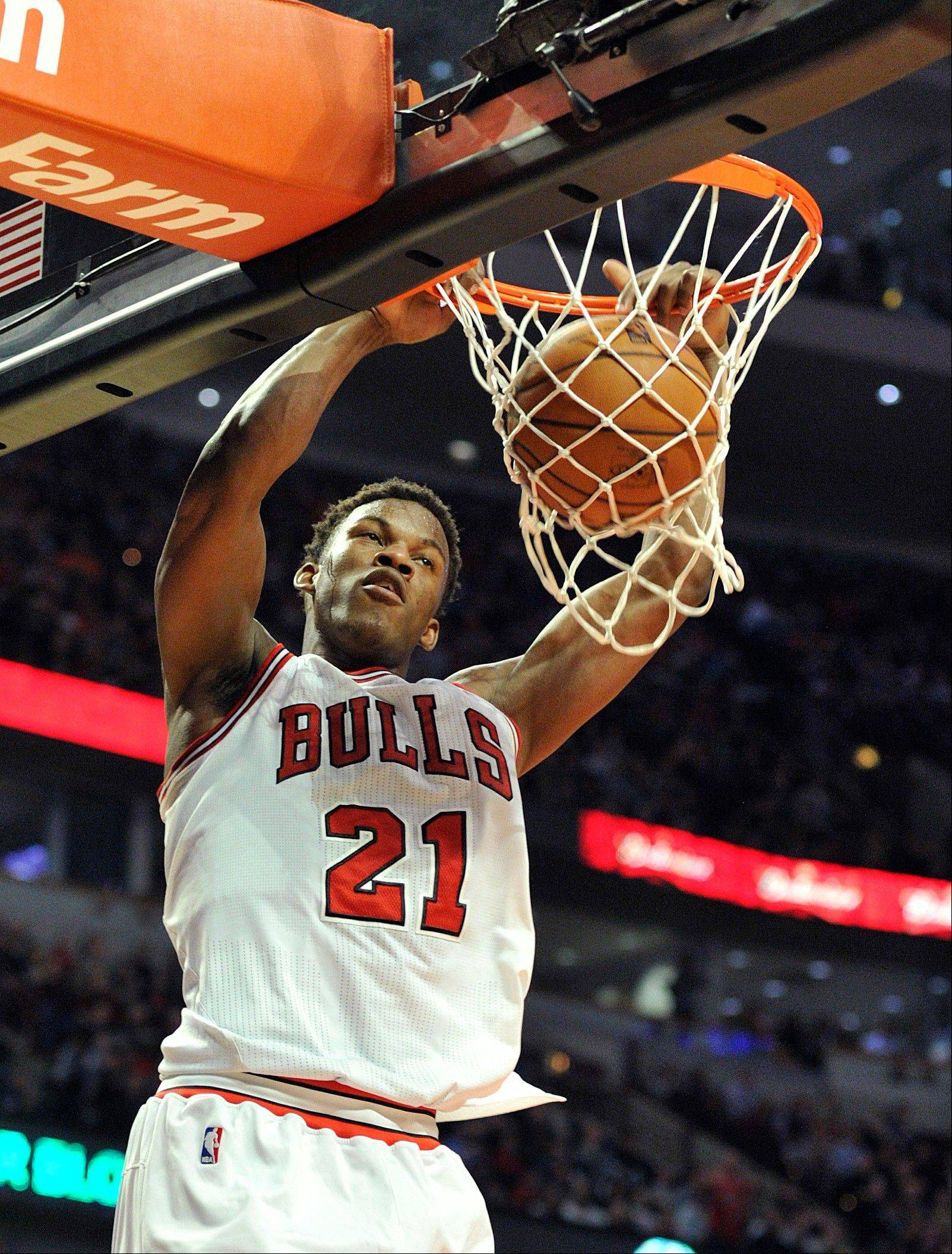 Chicago Bulls' Jimmy Butler (21) dunks the ball against the New York Knicks during the second half of an NBA basketball game, Thursday, April 11, 2013, in Chicago. The Bulls won 118-111 in overtime. (AP Photo/Jim Prisching)