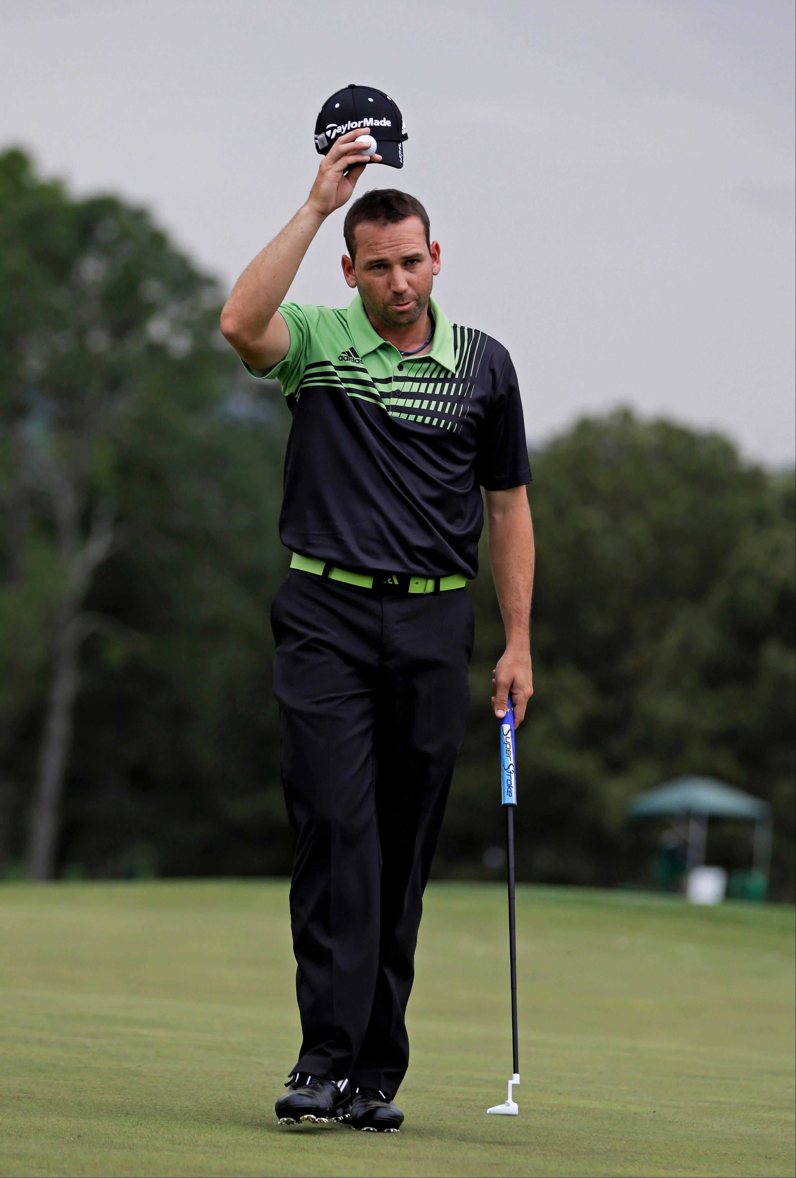 Sergio Garcia, of Spain, tips his cap on the 18th green after finishing the first round of the Masters golf tournament Thursday, April 11, 2013, in Augusta, Ga.