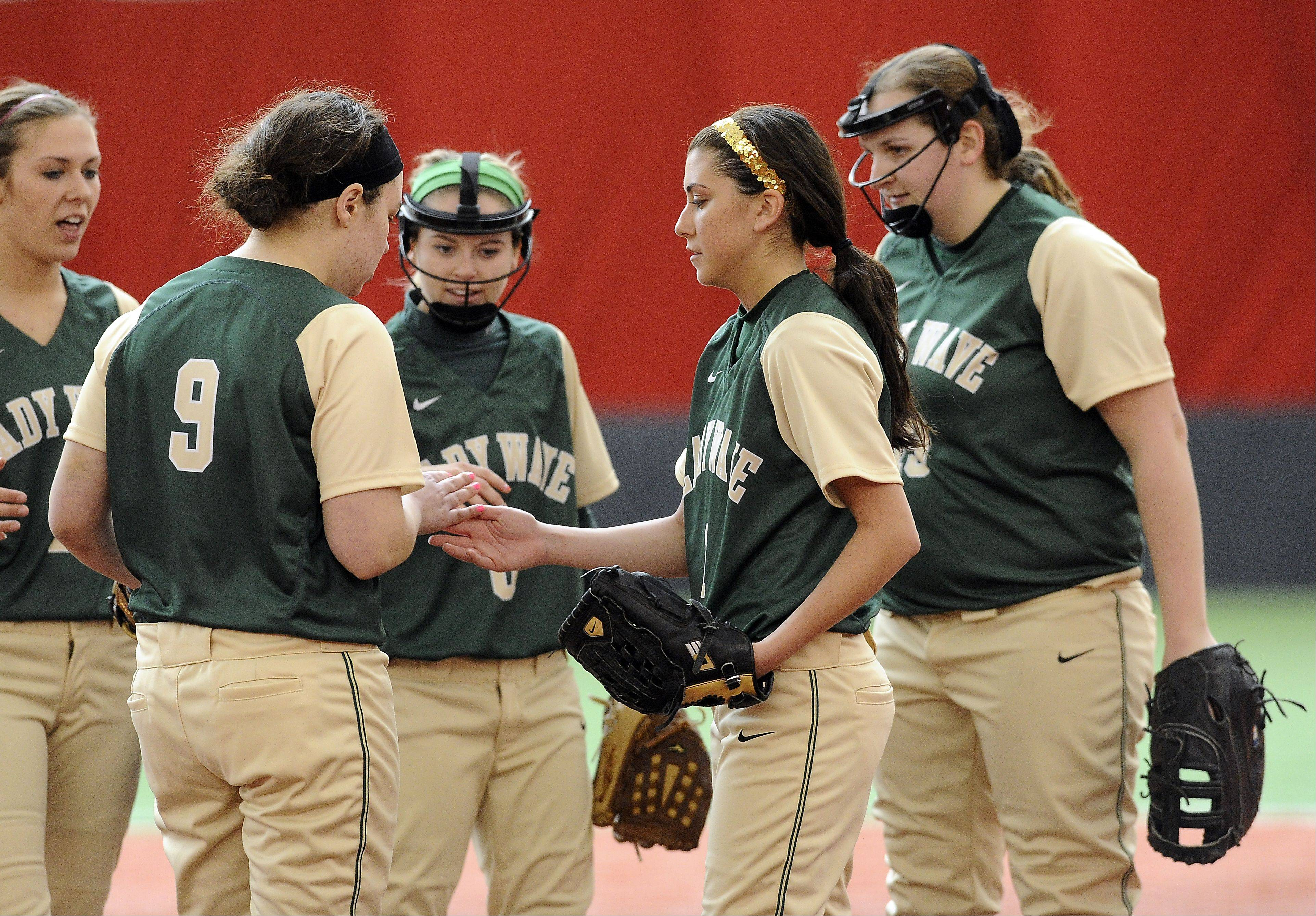 The St. Edward softball team gathers to talk things over during a game against Freeport in The Dome at The Ballpark in Rosemont earlier this season. The Green Wave host the 12th annual Chicagoland Challenge at the Elgin Sports Complex on Saturday.