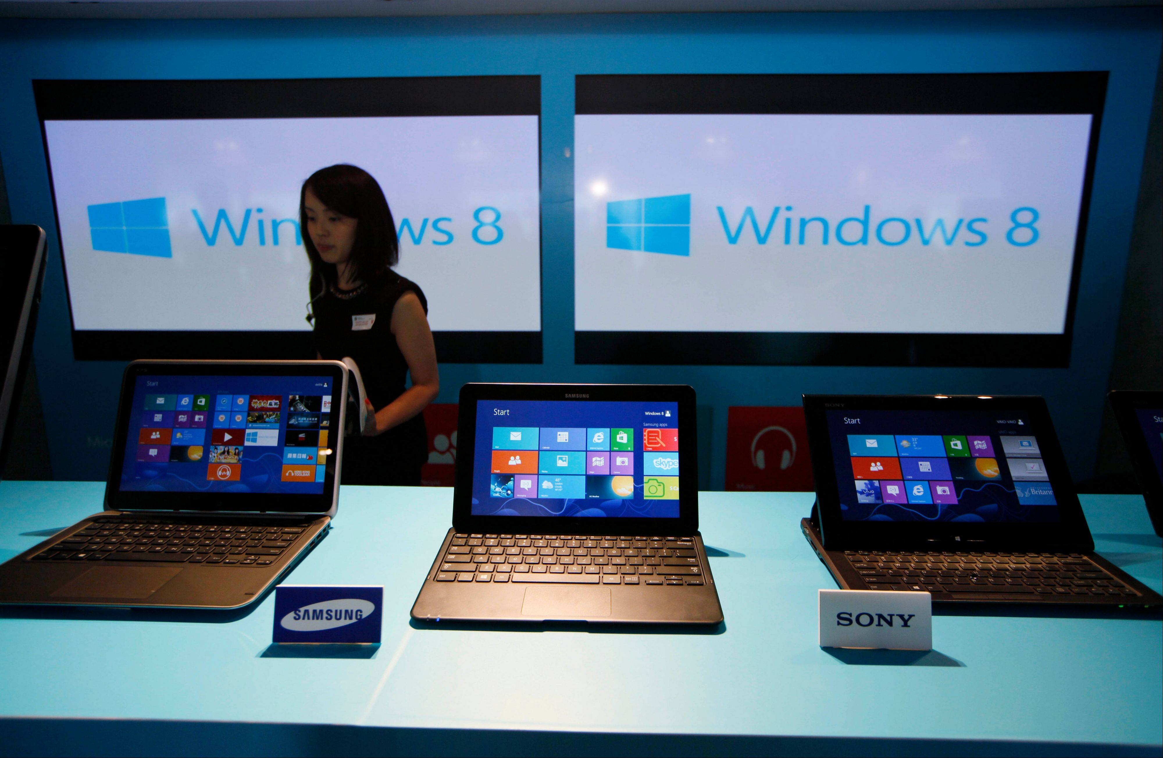 A woman walks past laptop computers running Microsoft Windows 8 operating system during its launching ceremony in Hong Kong. Research firm IDC says PC global shipments of PCs fell 14 percent in the first three months this year.