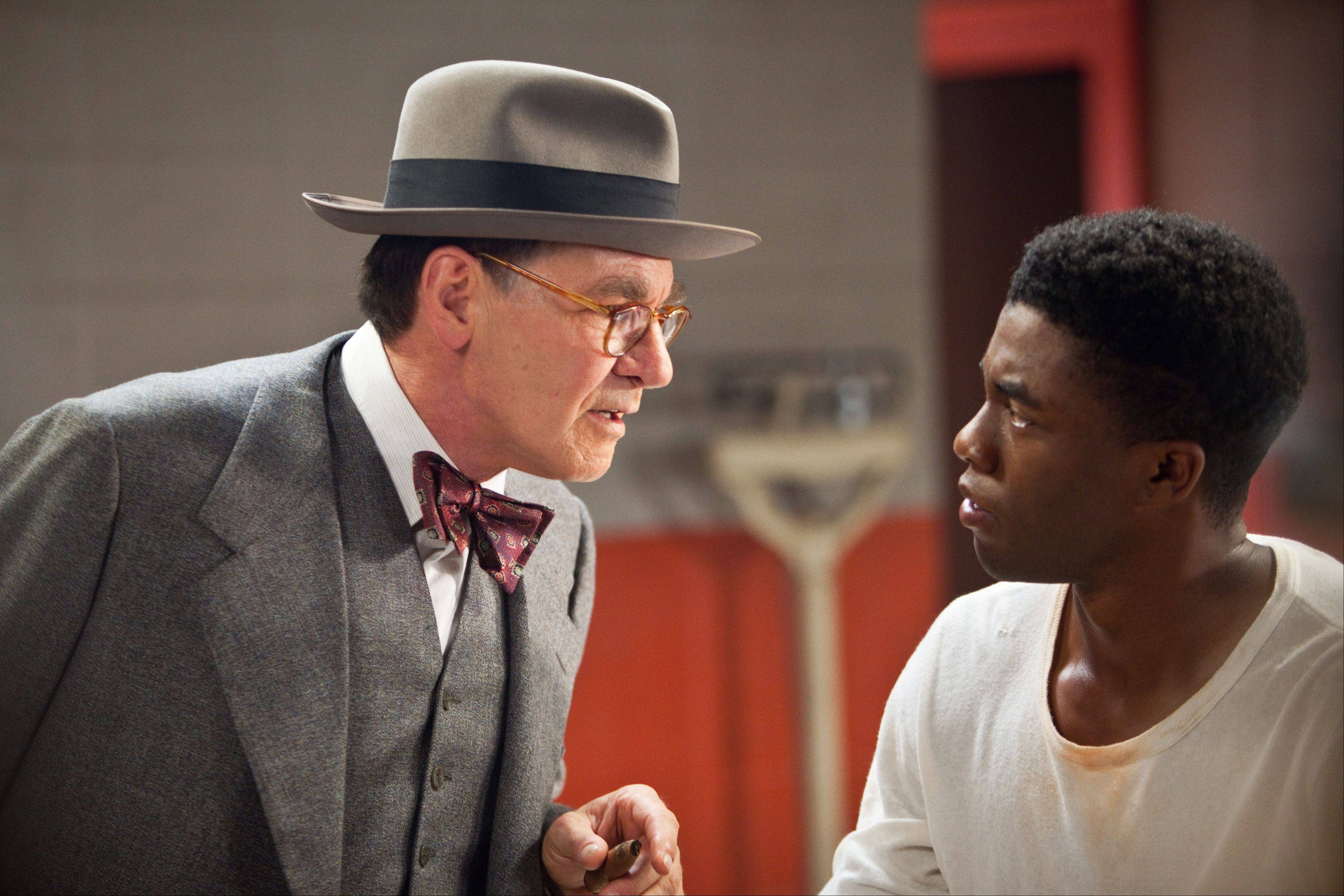 "Brooklyn Dodgers General Manager Branch Rickey (Harrison Ford) lectures Jackie Robinson (Chadwick Boseman) on sportsmanship in the fact-based sports drama ""42."""