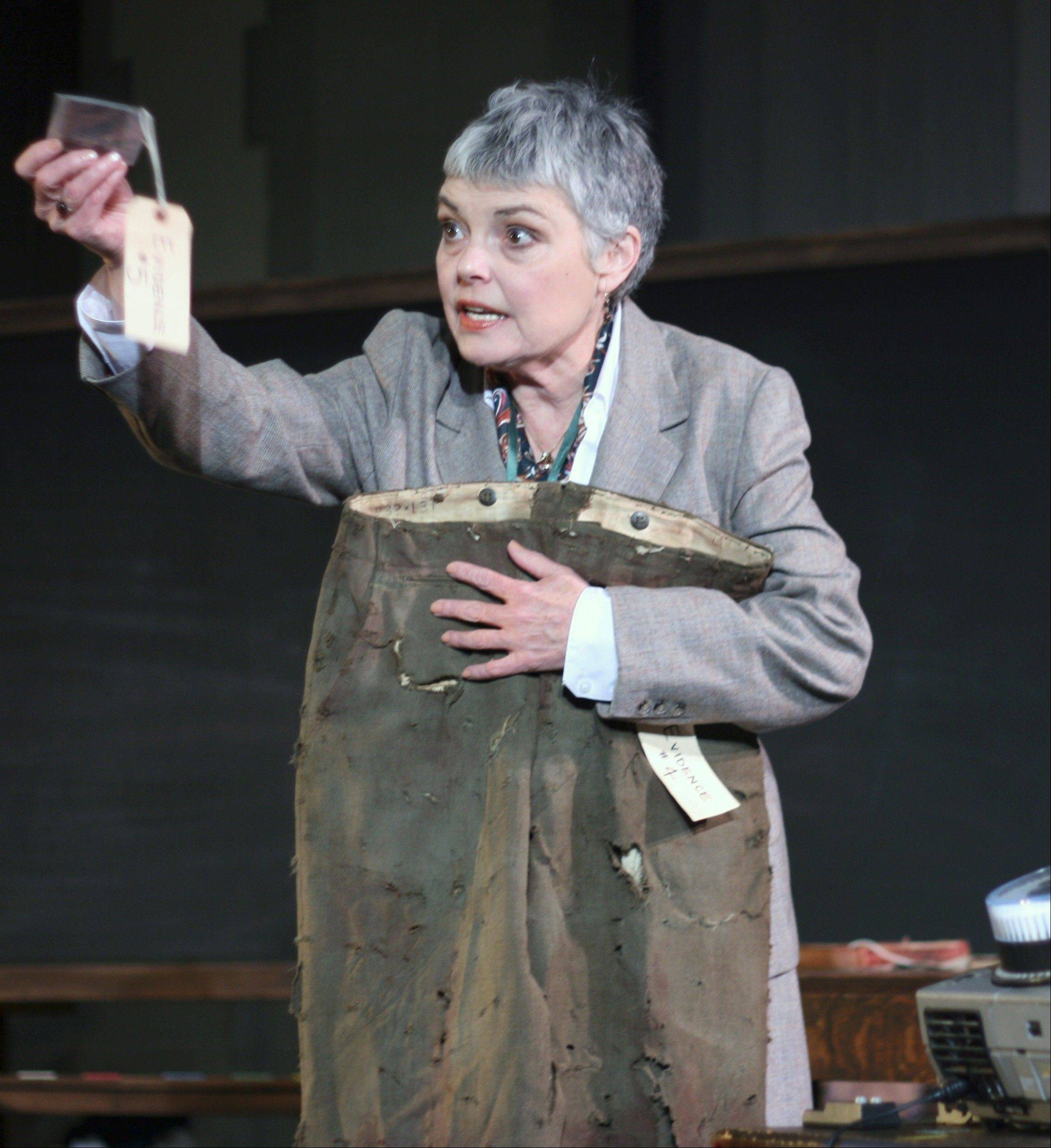 "Kristine Thatcher stars as a Dutch librarian who travels the world in pursuit of the mysterious stranger who returned a travel guide 113 years after its due date in First Folio Theatre's production of Glen Berger's ""Underneath the Lintel."""