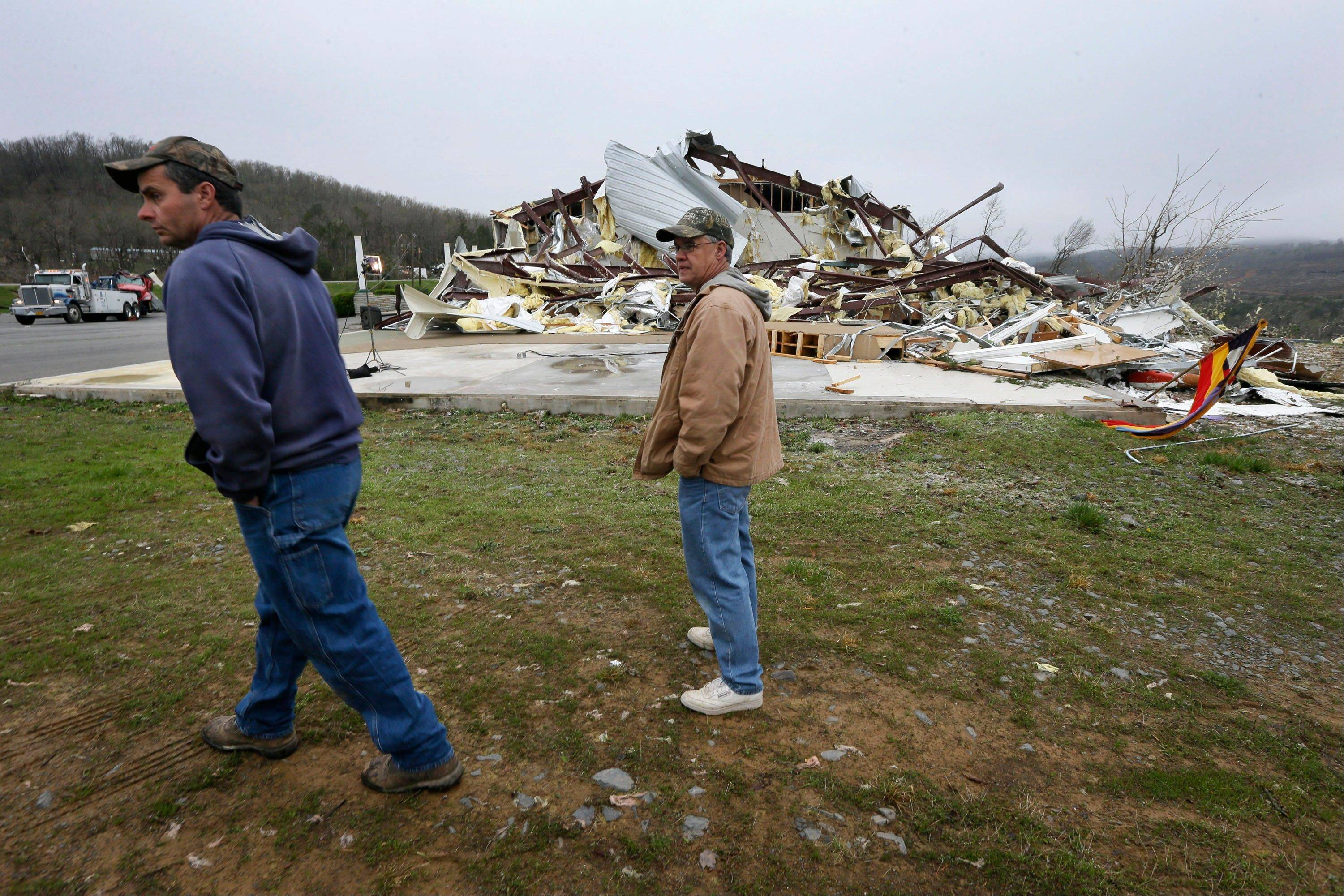 Larry Gammill, left, who attends Botkinburg Foursquare Church, and his friend Tim Parks walk from what is left of the church in Botkinburg, Ark., Thursday, April 11, 2013 after a severe storm struck the building late Wednesday. The National Weather Service is surveying areas Thursday to determine whether tornadoes or strong winds caused damage.