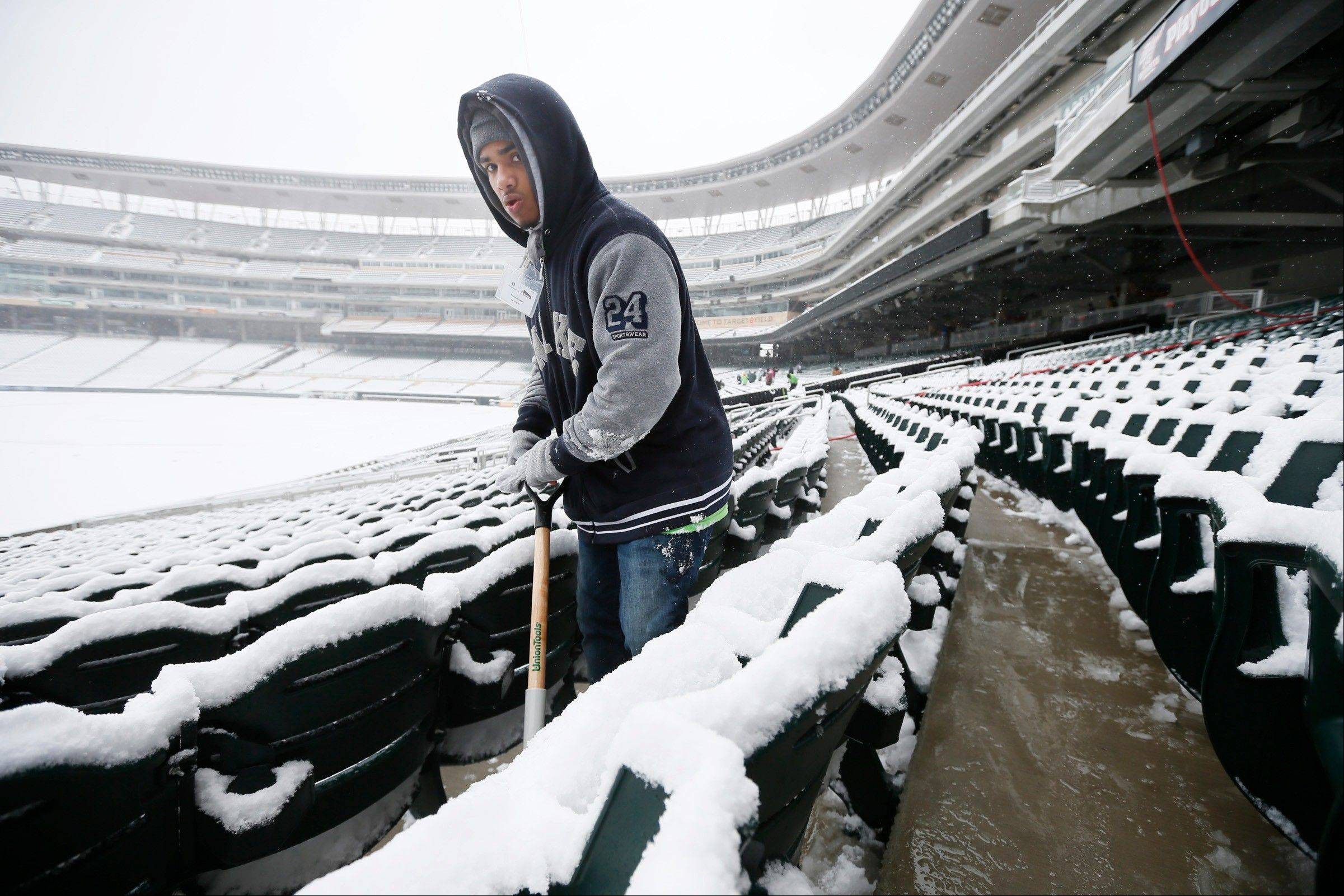 Kashaun Gage removes snow form Target Field on Thursday, April 11, 2013 in Minneapolis. A spring storm packing snow and ice has hit several states in the Midwest, knocking out power in communities and prompting Minnesota's governor to call out the state National Guard to help residents.