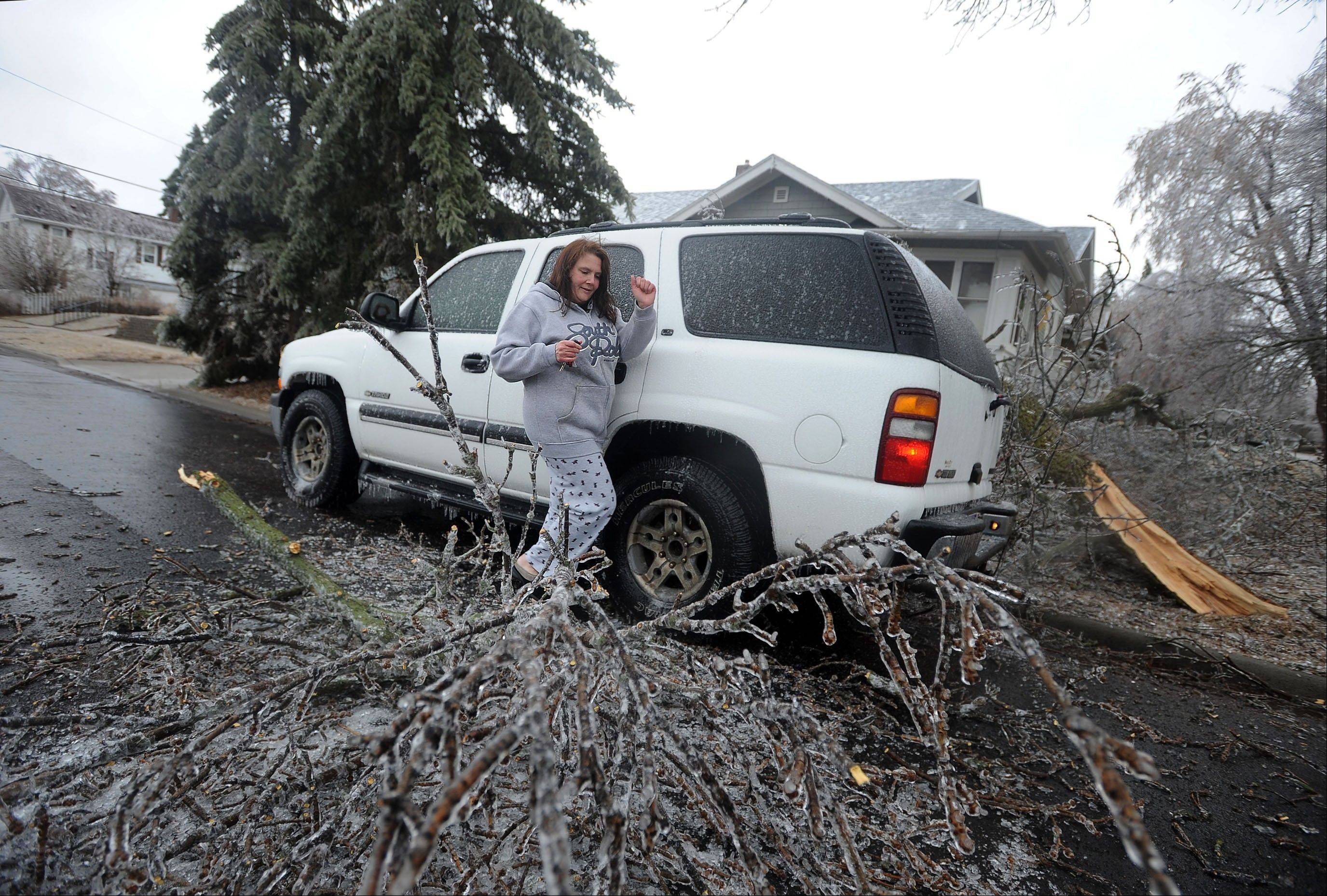 Dianne Dansman maneuvers around a fallen tree that came inches away from falling on her SUV on Tuesday, April 9, 2013 in Sioux Falls, S.D. Freezing rain in the morning downed trees and caused power outages throughout the city.
