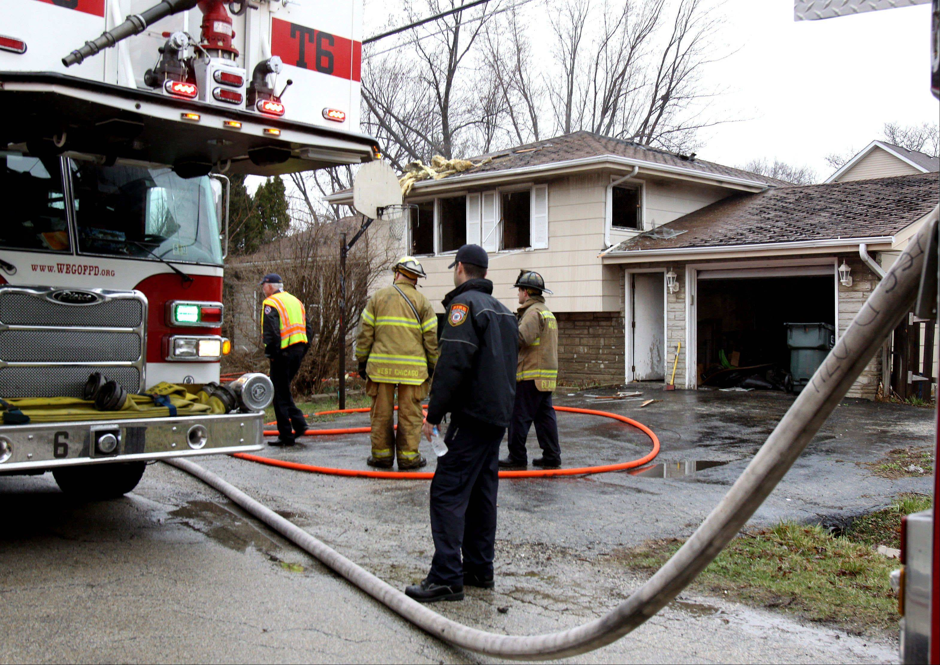 Wheaton firefighters clean up after a house fire Thursday morning on Armbrust Avenue.