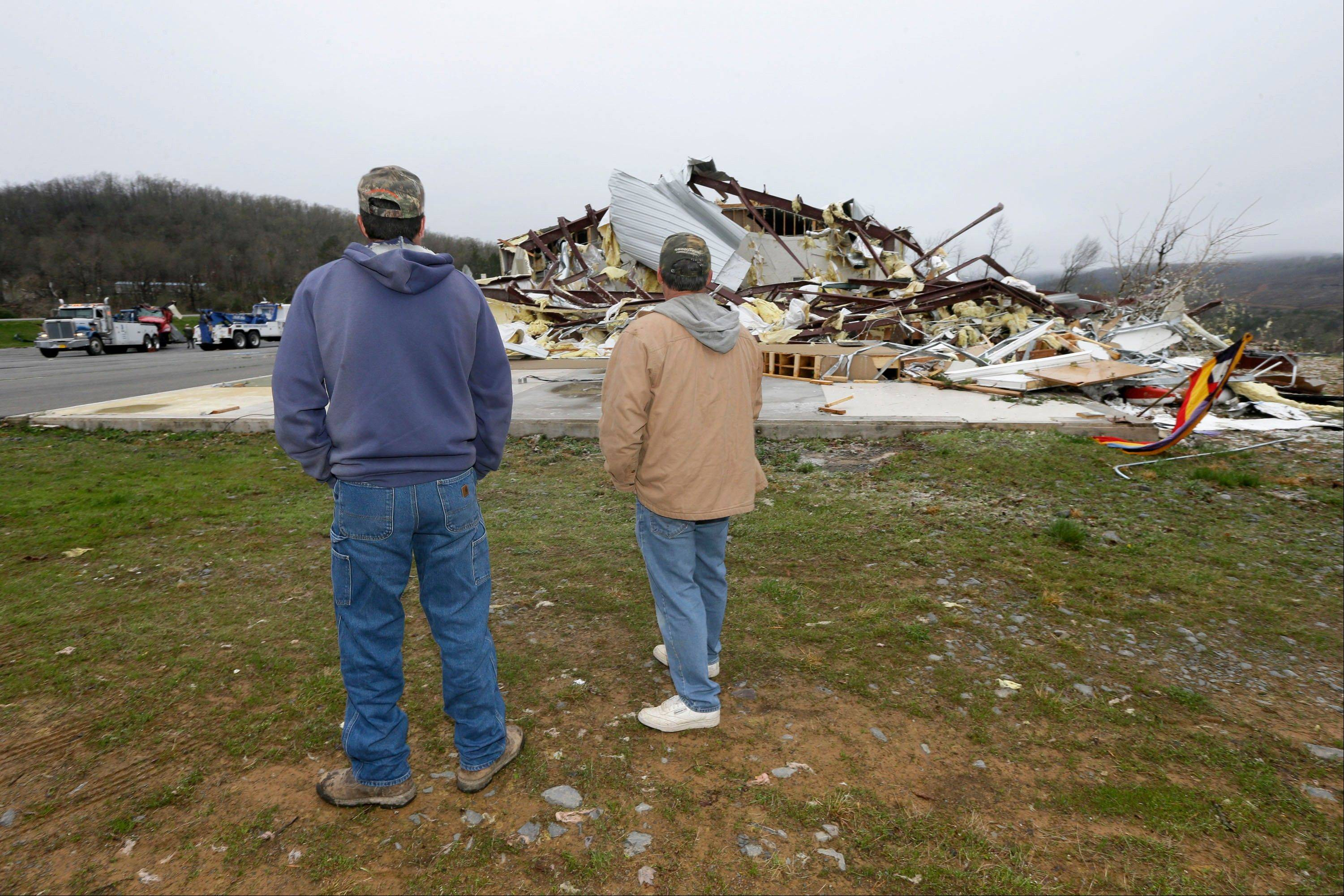Larry Gammill, left, and Tim Parks survey tornado damage at Botkinburg Foursquare Church in Botkinburg, Ark., Thursday, April 11, 2013, after a severe storm struck the building late Wednesday.