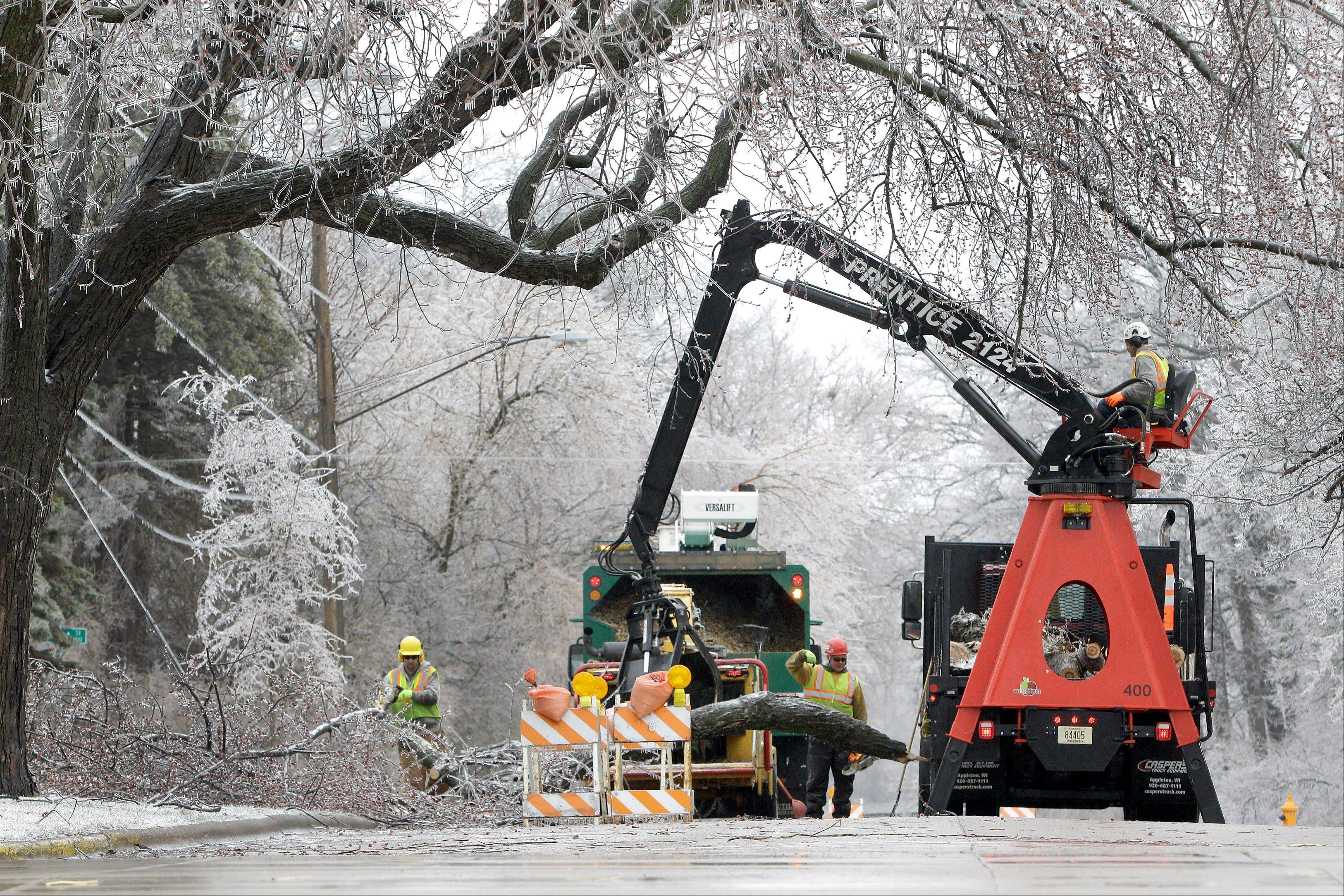 Public works employees remove large fallen tree branches coated in heavy ice Wednesday in Appleton, Wis. A wintry mix of rain, ice and snow in Wisconsin is making travel difficult and has put tens of thousands without power.