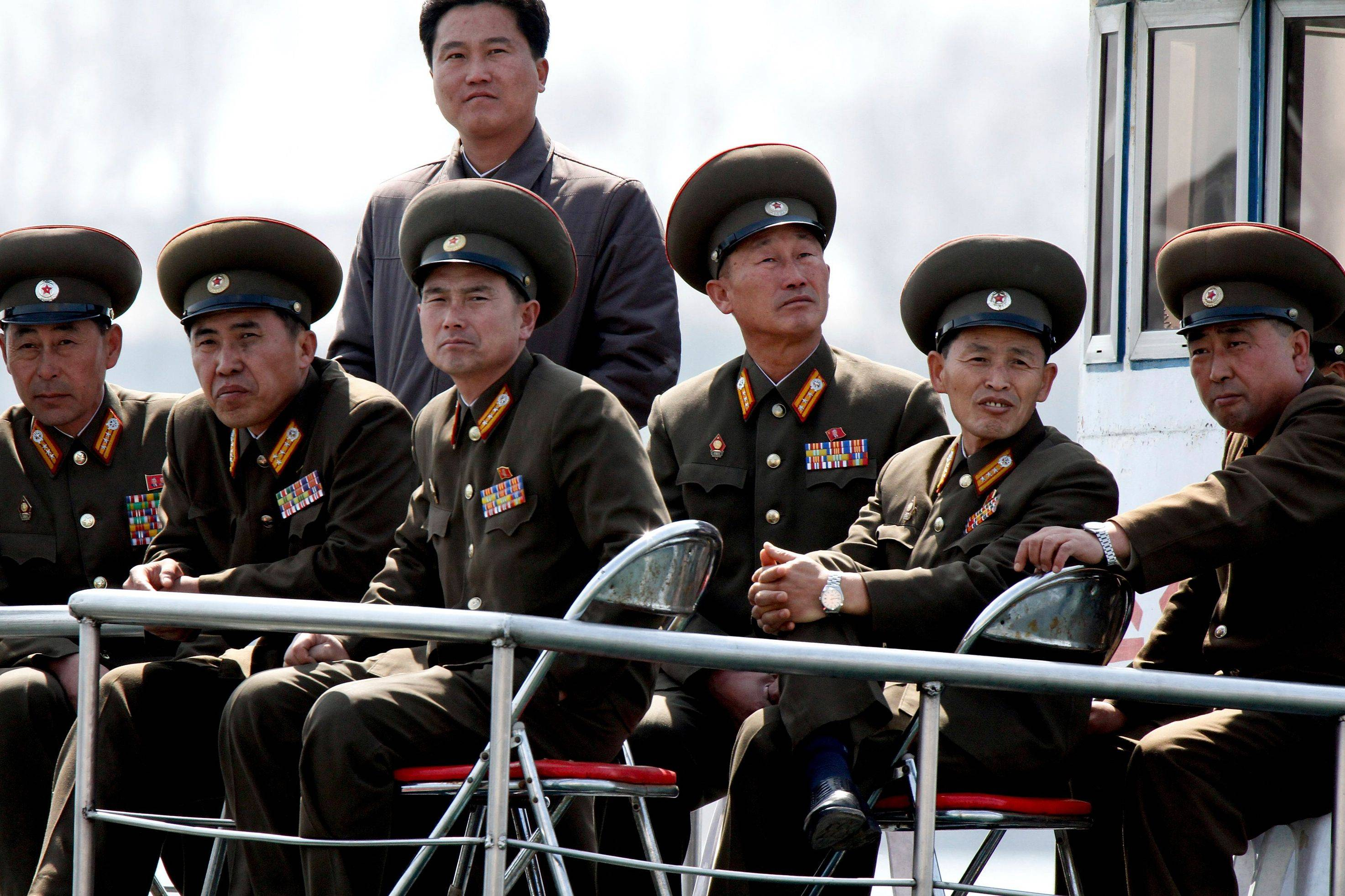 "North Korean military officers look from a sightseeing boat sailing on the Yalu River, the China-North Korea border river. North Korea delivered a fresh round of rhetoric Thursday with claims it had ""powerful striking means"" on standby for a missile launch."