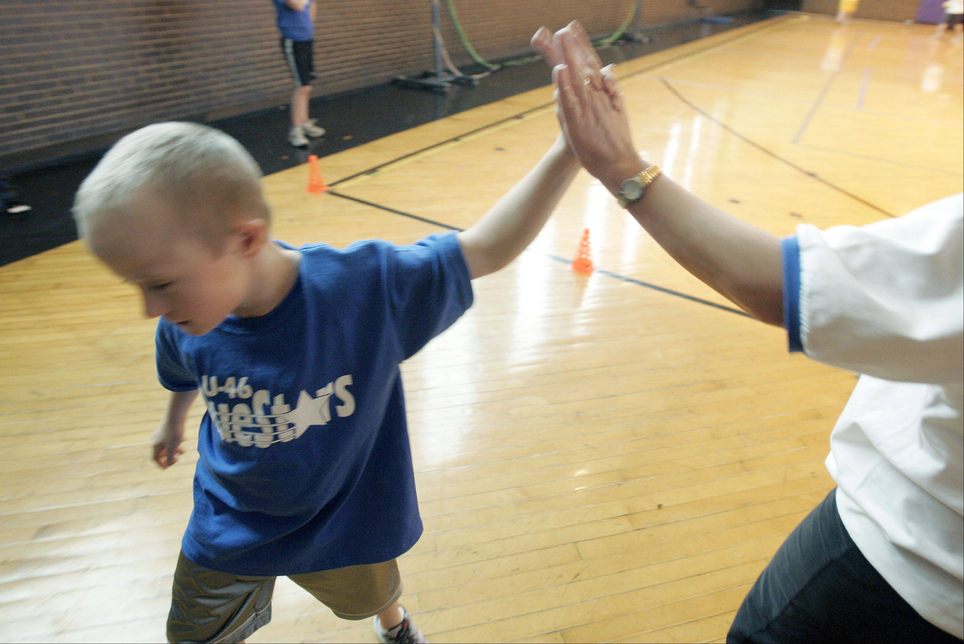 Ian Fergus collects a high-five after his performance in the softball throw during practice.