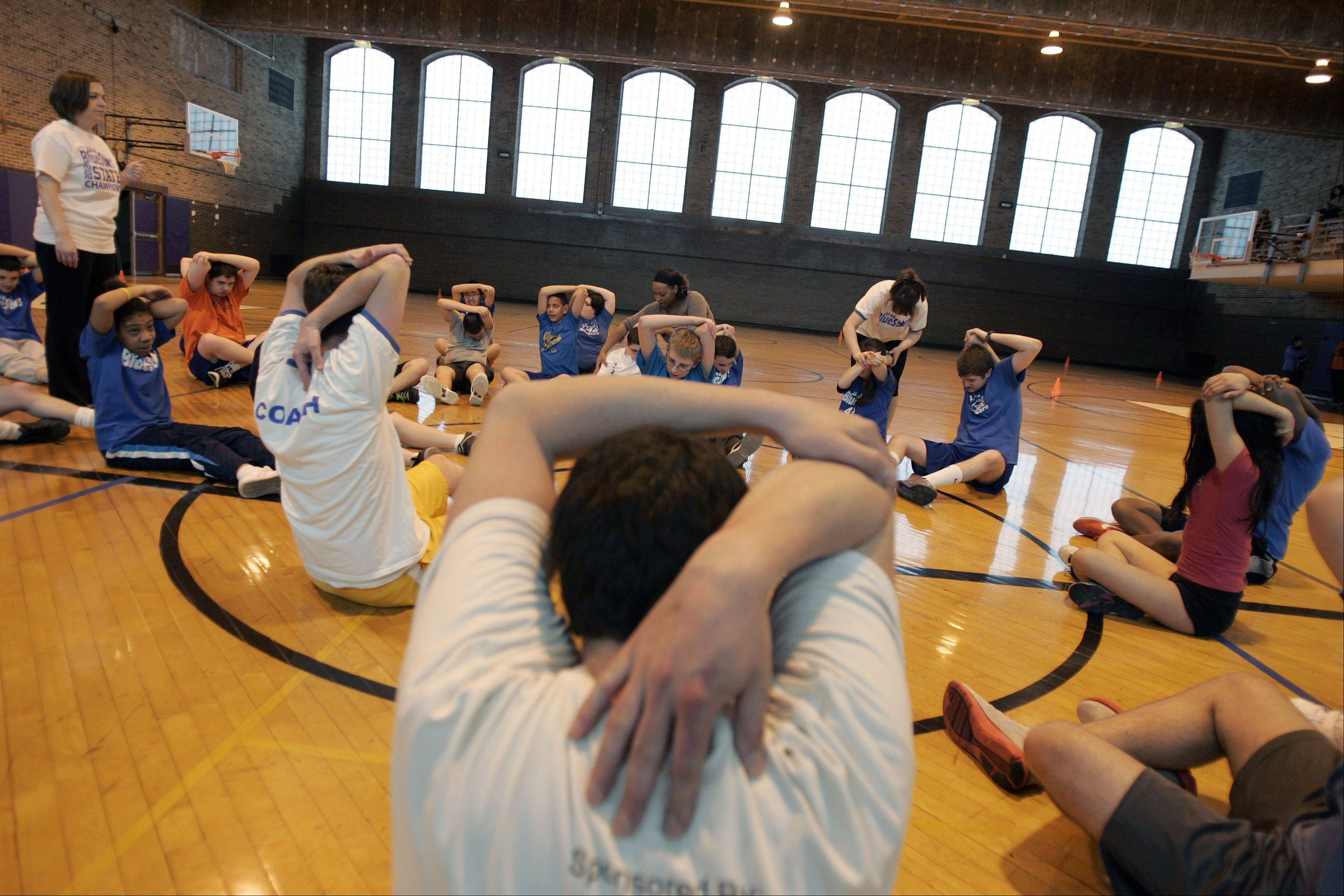 Students and coaches stretch during practice for the Elgin Area School District U-46 BlueStars.