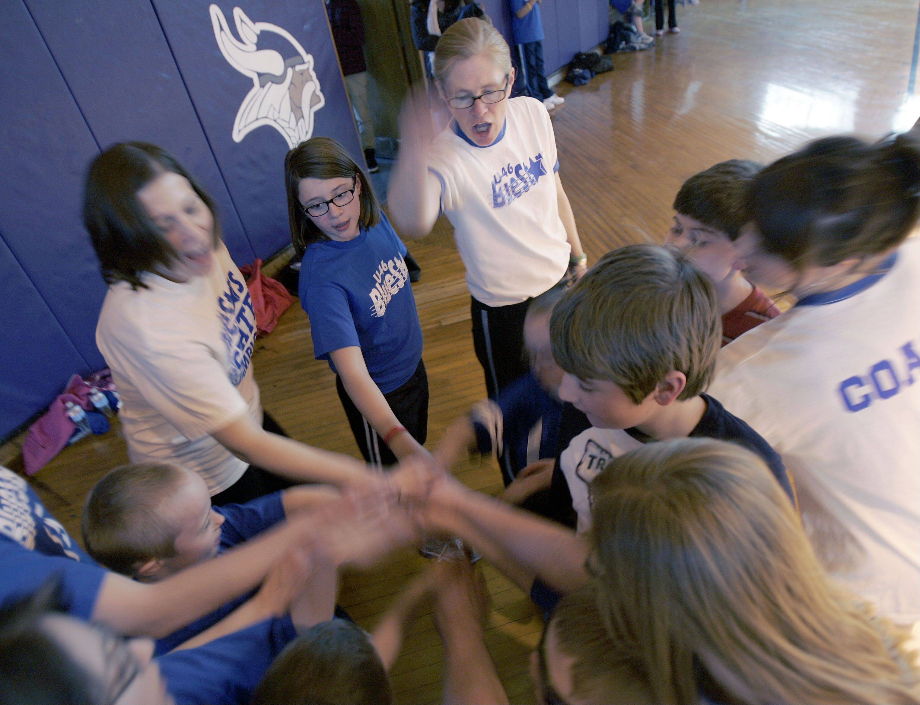 Special Olympics coordinator Maureen Lue, top center, gathers a group of her athletes as they get fired up for a BlueStars practice.