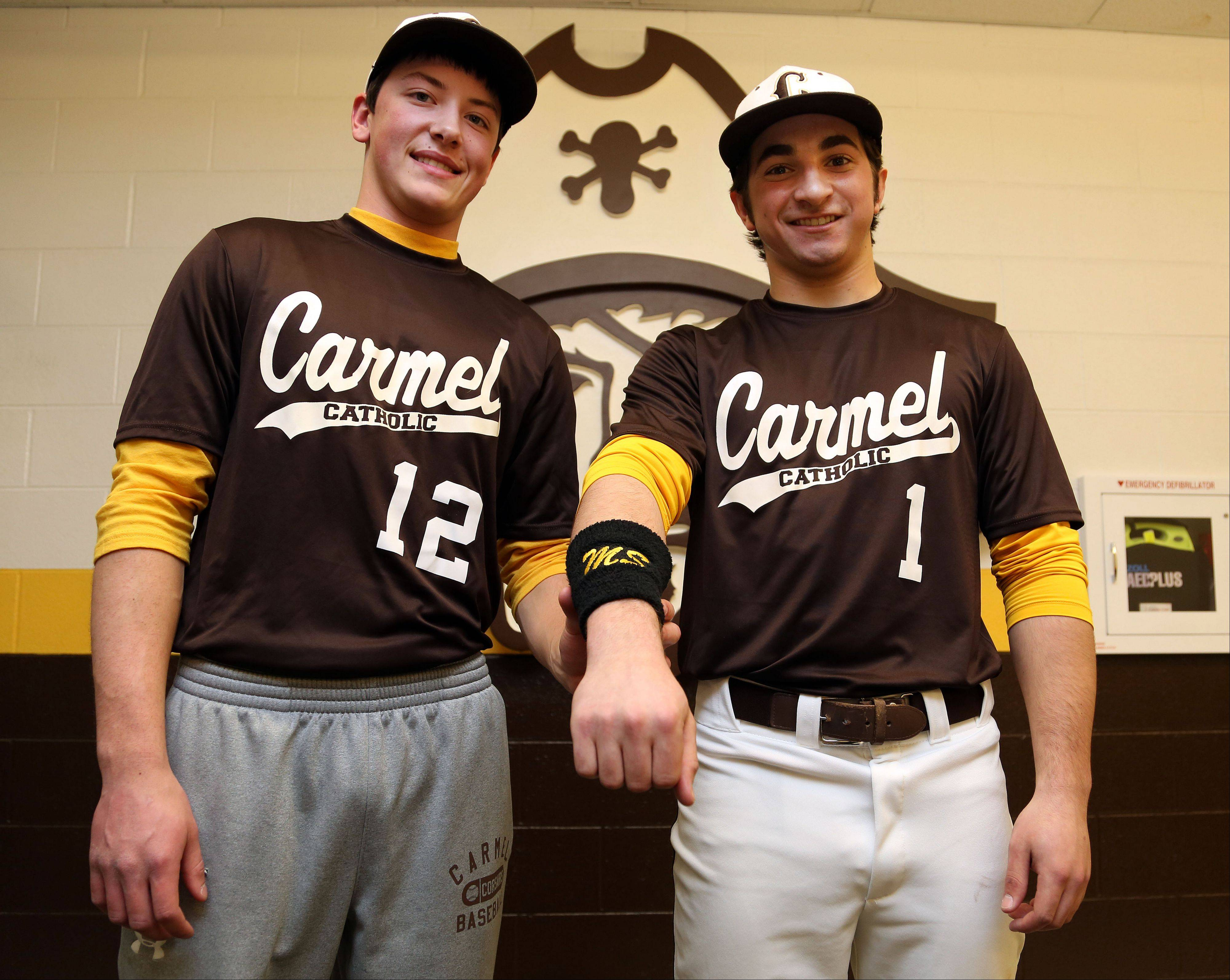 Carmel senior baseball player Matt Schafer, left, displays the wristbands bearing his initials that teammate Brett Milazzo designed.