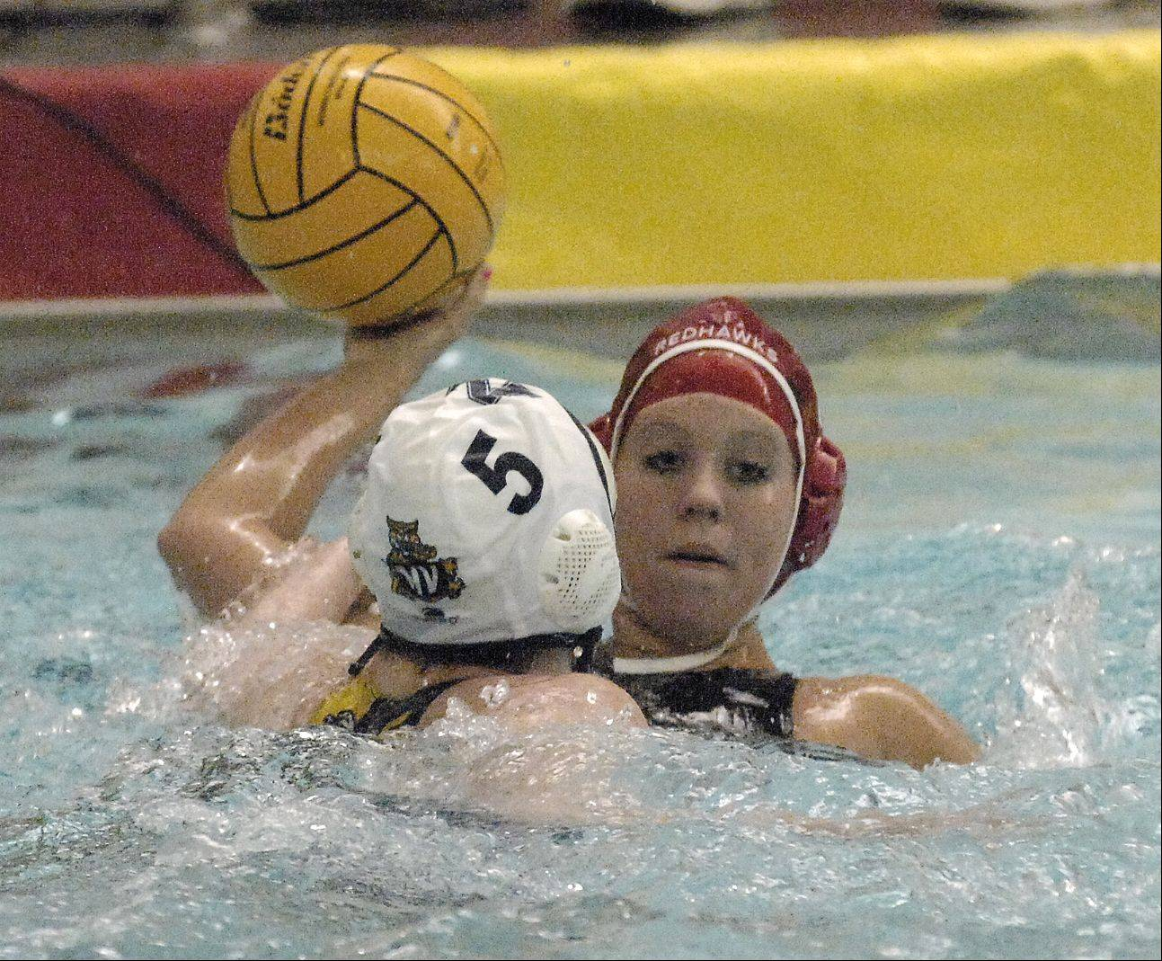 Jenny Doyle of Naperville Central looks to pass the ball around Broke Bedford of Neuqua Valley battle for control of the ball during varsity girls water polo at Central, Thursday.