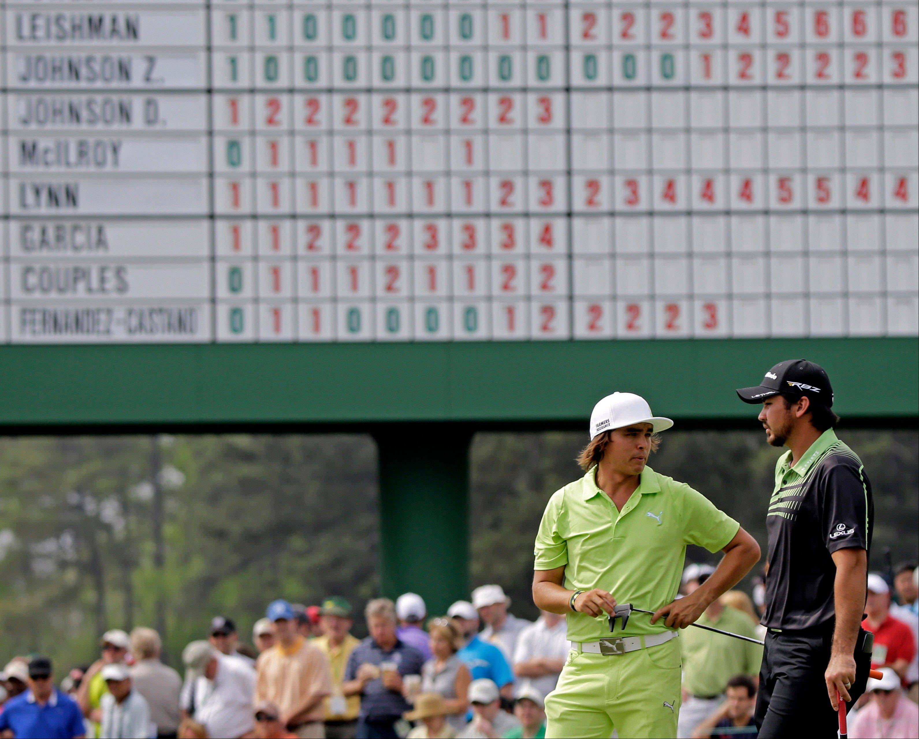 Rickie Fowler, left, chats with Jason Day, of Australia, on the 17th green during the first round of the Masters golf tournament Thursday, April 11, 2013, in Augusta, Ga.