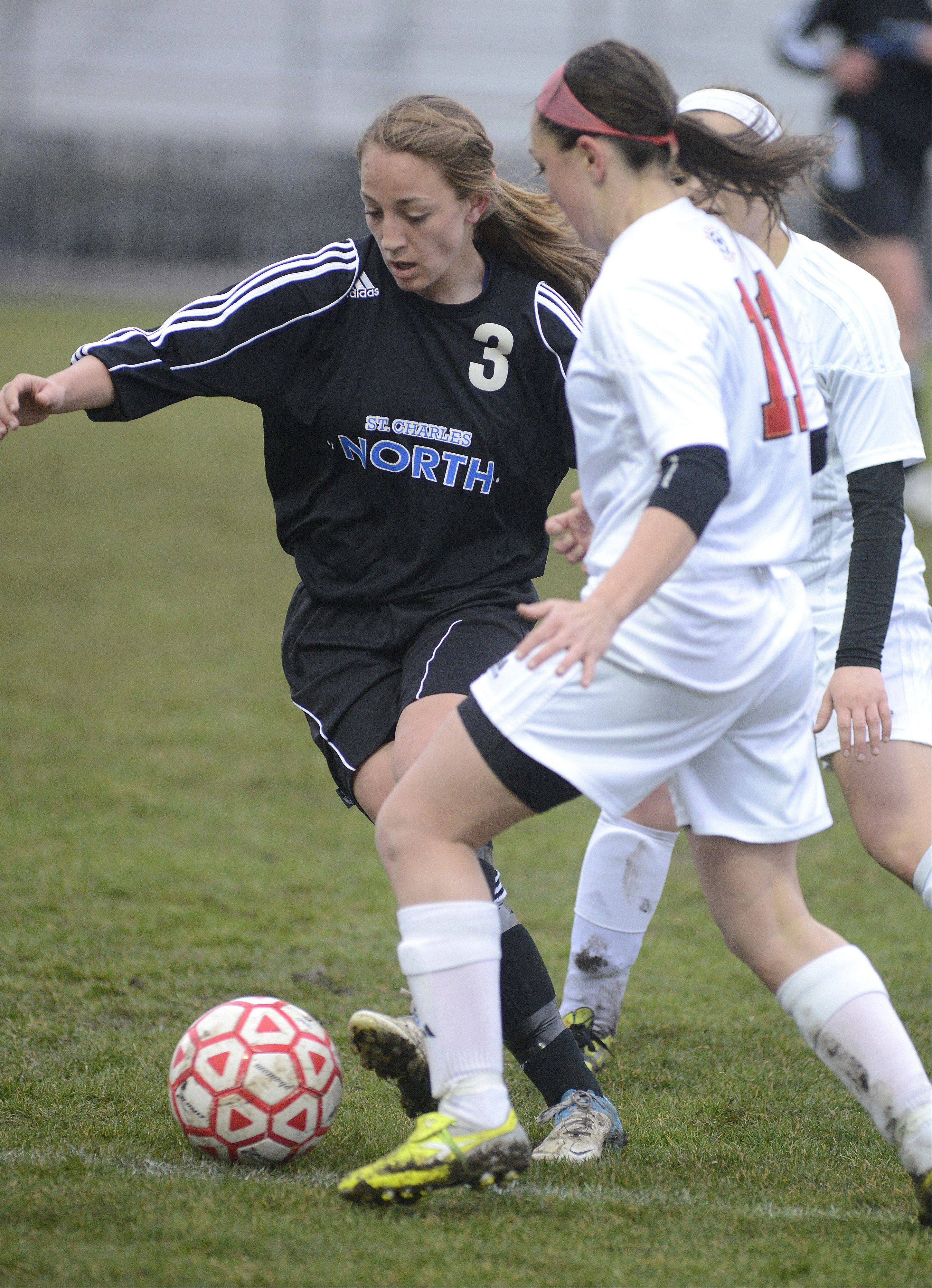St. Charles North's Alex Gage and Batavia's Lindsay Spears battle for the ball in the first half on Thursday, April 11.