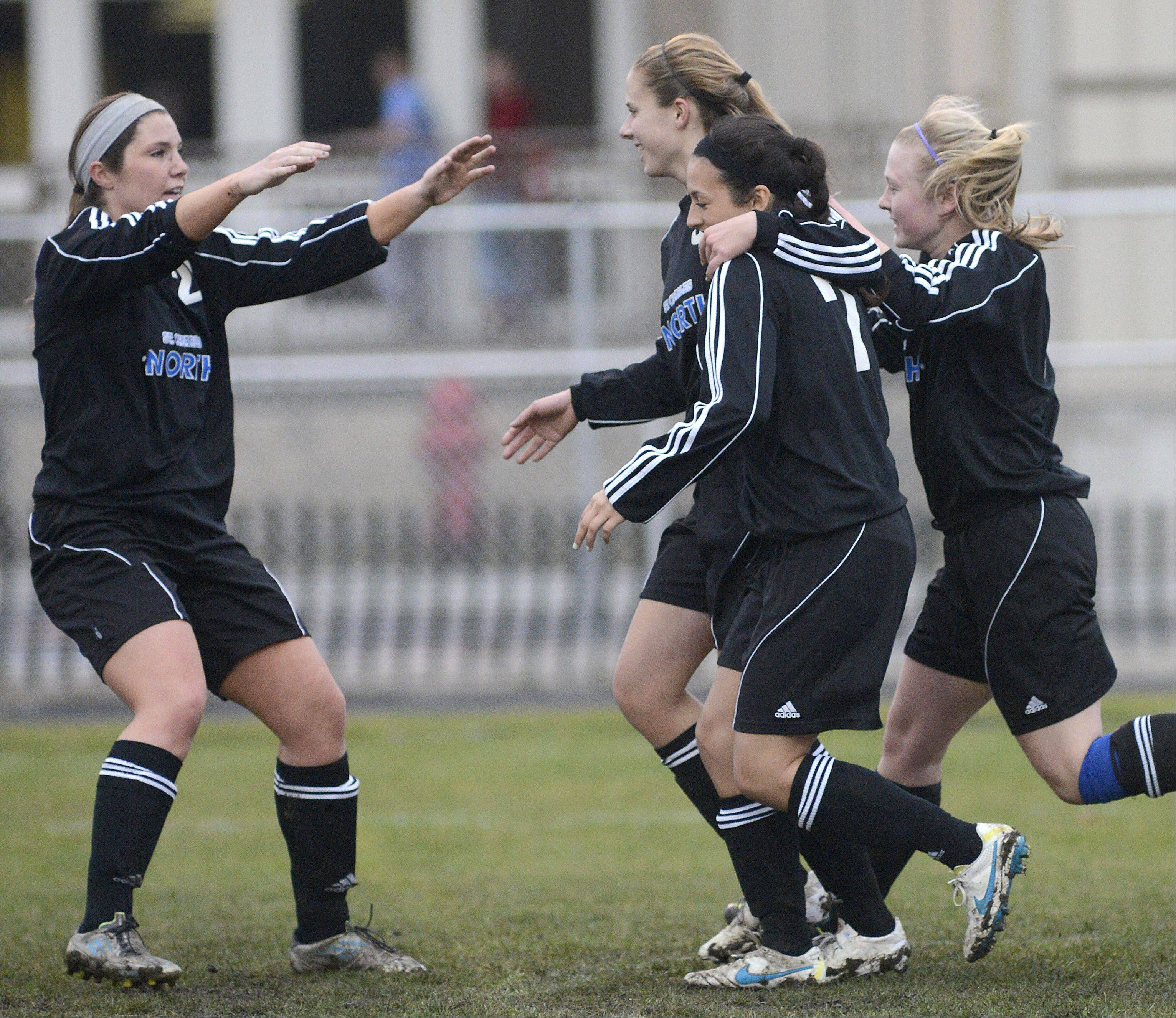 St. Charles North's Kenzie Rose, left, congratulates Alyssa Brandt, center, after her goal in the first half as she runs back to center field flanked by Ashlyn Walter and Natalie Winkates on Thursday, April 11.