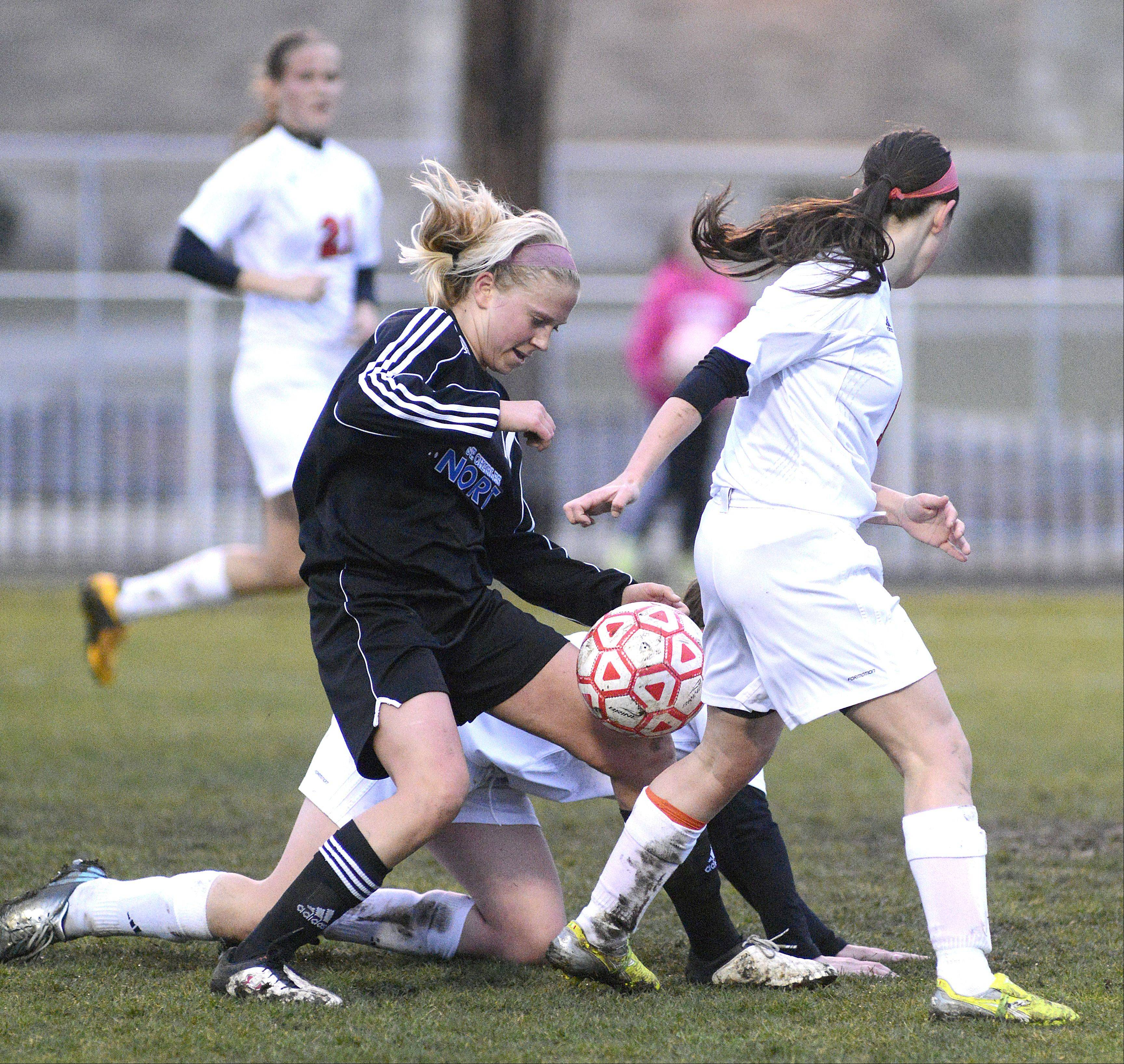 St. Charles North's Kelly Manski is the victor of the ball as Batavia's Alison Grimm goes down and Lindsay Spears (11) continues the fight in the first half on Thursday, April 11.