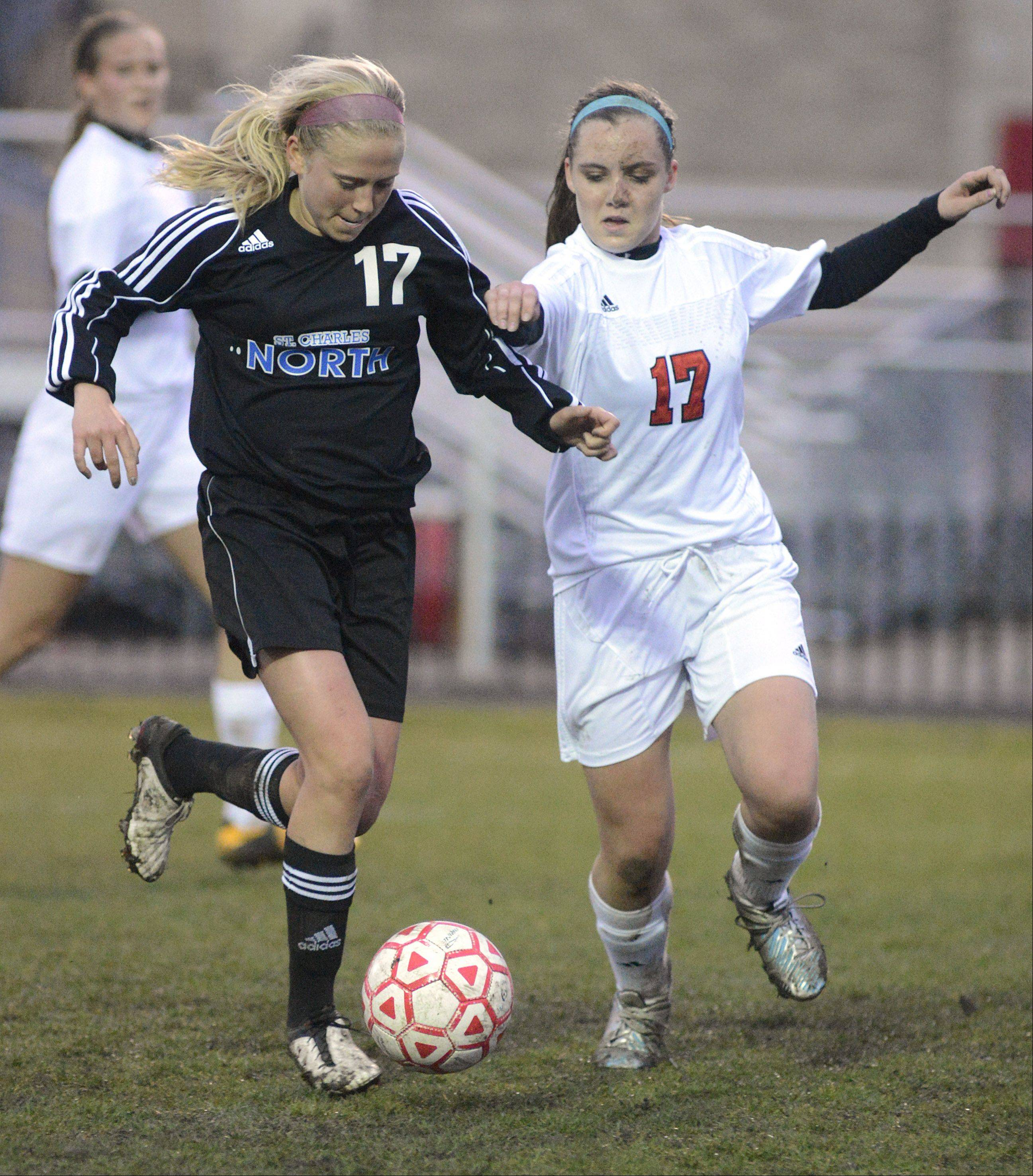 St. Charles North's Kelly Manski and Batavia's Alison Grimm battle for the ball in the first half on Thursday, April 11.