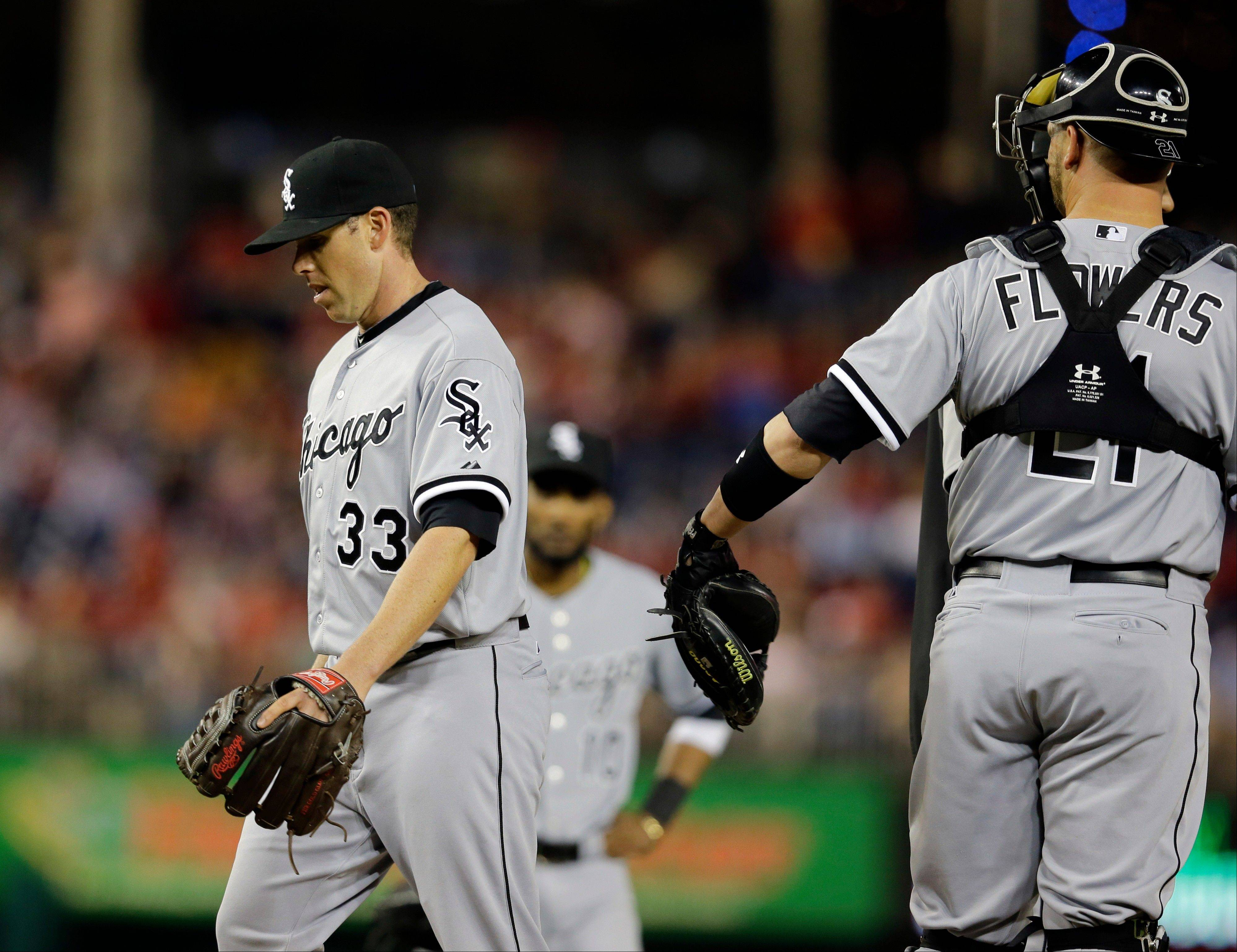 Chicago White Sox starting pitcher Dylan Axelrod (33) walks to the dugout past catcher Tyler Flowers as he is relieved during the fourth inning of an interleague baseball game against the Washington Nationals at Nationals Park, Thursday, April 11, 2013, in Washington.