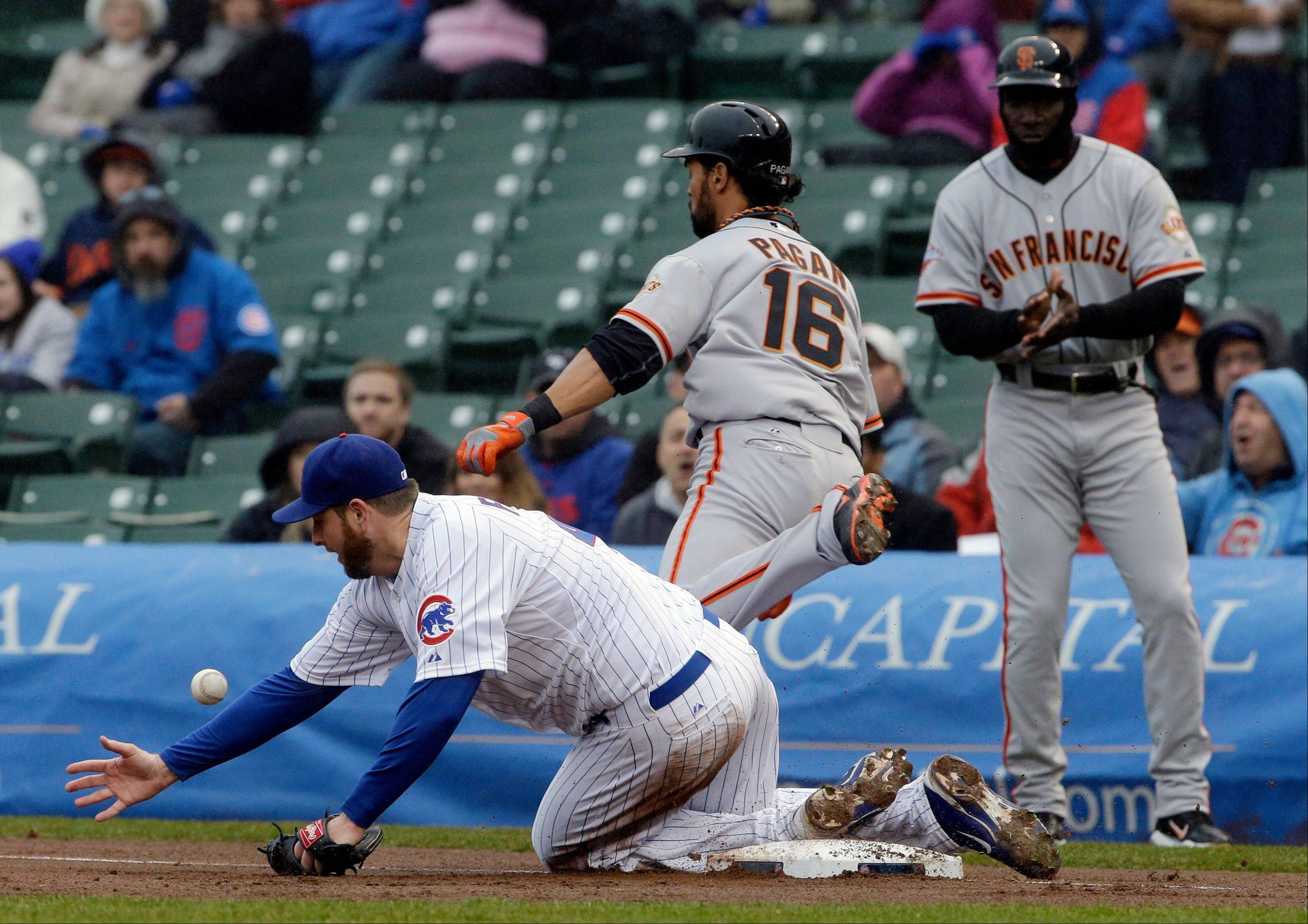 Chicago Cubs starter Scott Feldman, bottom, can't make the catch from first baseman Anthony Rizzo as San Francisco Giants' Angel Pagan(16) is safe at first base during the first inning of a baseball game in Chicago, Thursday, April 11, 2013.