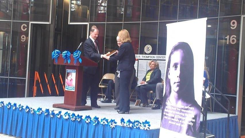 Roy Harley (left) of Prevent Child Abuse Illinois presents award to Sally Foster (center) and Laura Notson (right) on April 1st at Child Abuse Prevention Month kick-off, held at James R. Thompson Center in Chicago.