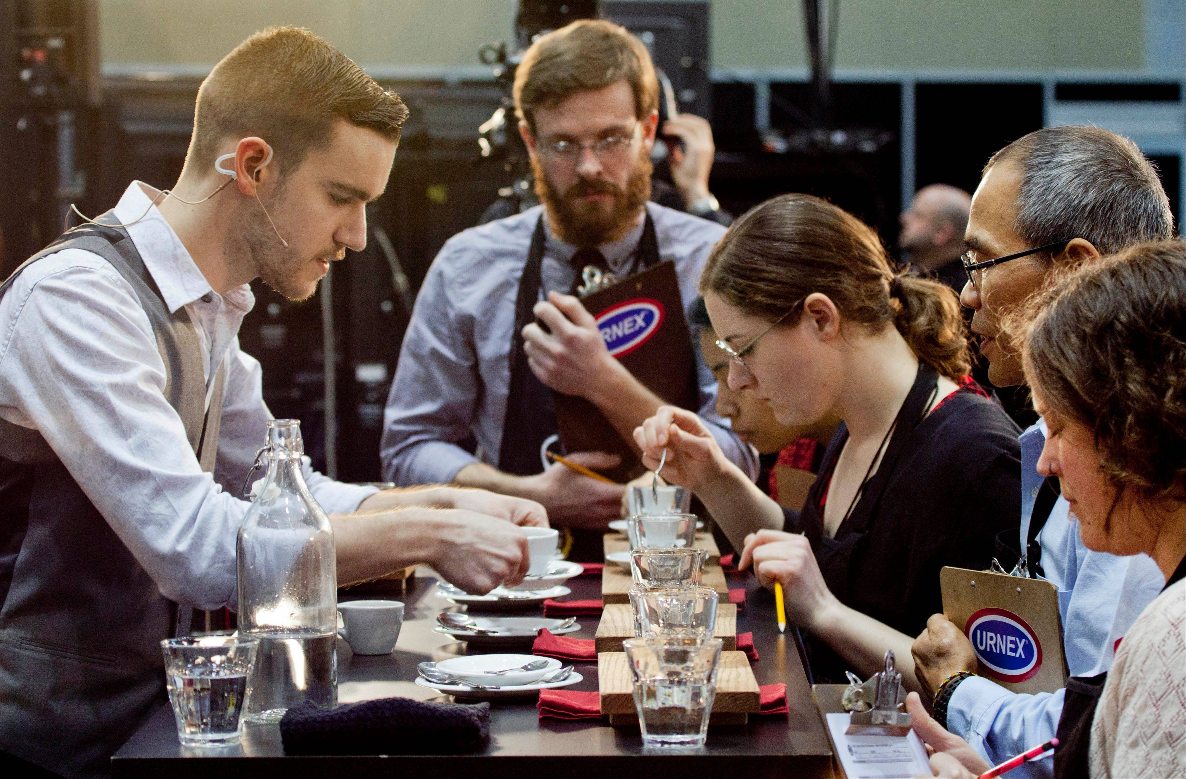 Barista competitor Nick Purvis, left, of Santa Barbara, Calif., presents one of his brewed entries to a panel of judges at the annual United States Barista Championship in Boston. Participants have 15 minutes to prepare and serve four espressos, four cappuccinos and four signature beverages, as they compete for a chance to go to the world championship in Melbourne, Australia.