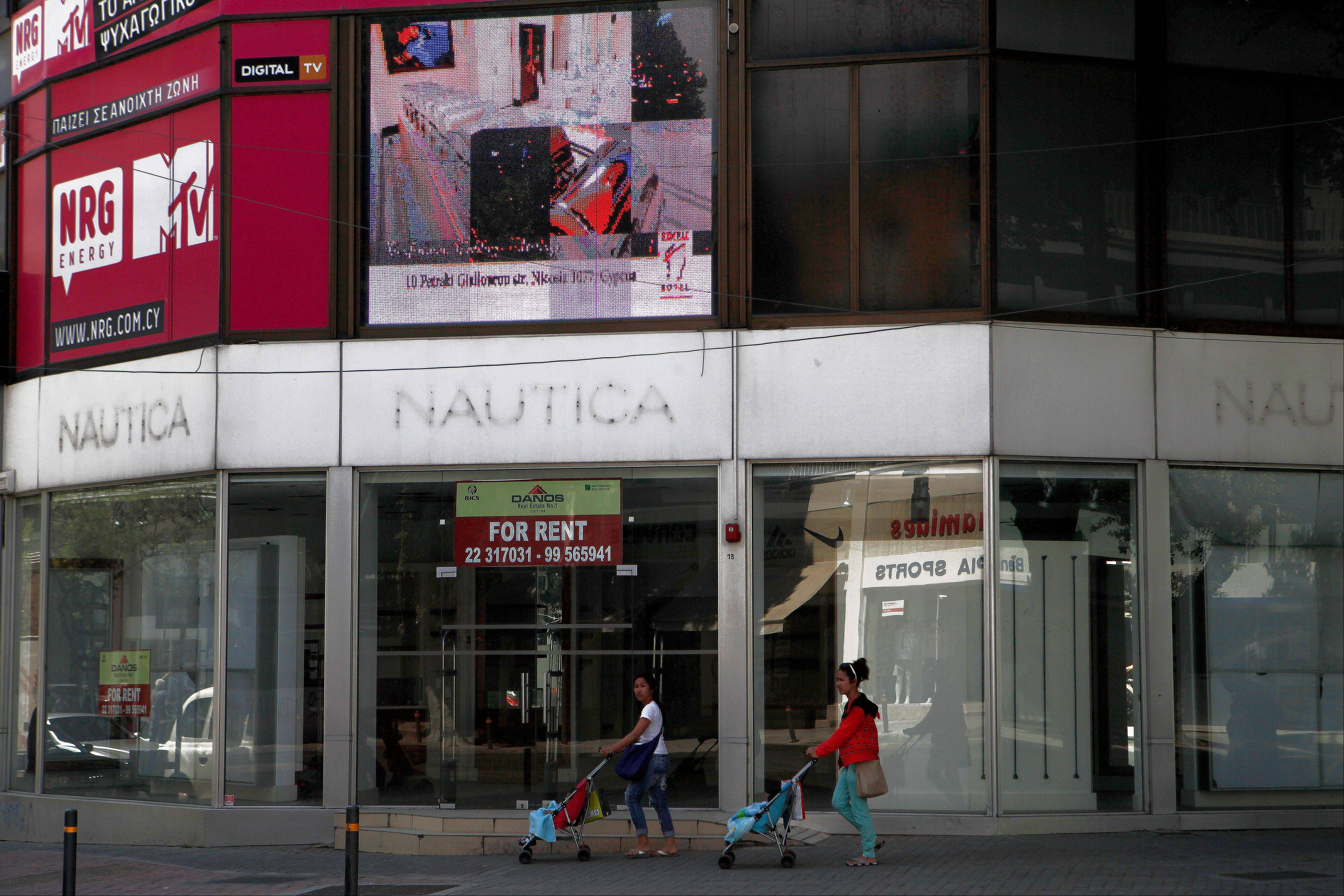 Two women with their child walk outside of an empty closed shop at a main shopping street in central capital Nicosia, Cyprus, Friday, April 12, 2013. President Nicos Anastasiades said that he will dispatch letters to EU Commission President Jose Manuel Ba.