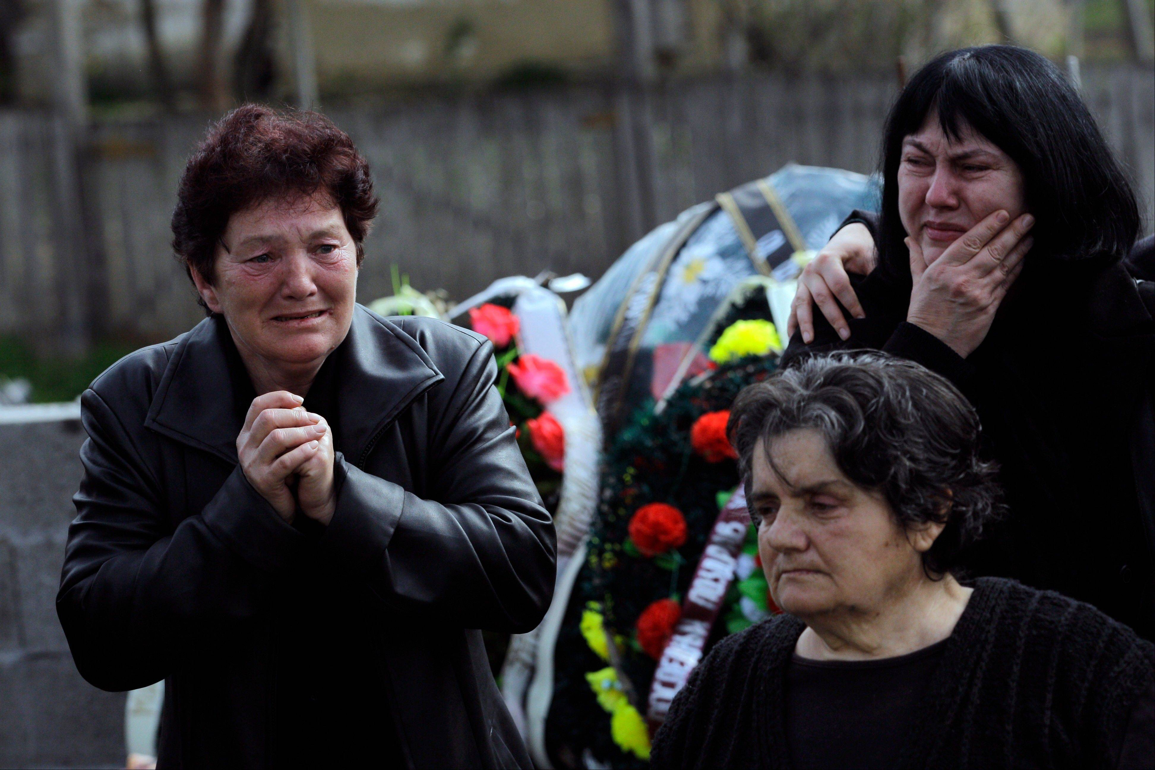 People react prior to a mass funeral of the victims of a shooting in the village of Velika Ivanca, some 30 miles southeast of Belgrade, Serbia, Friday, April 12, 2013. The village is preparing for the funerals of thirteen victims of a shooting that happened on Tuesday, April 9, 2013.