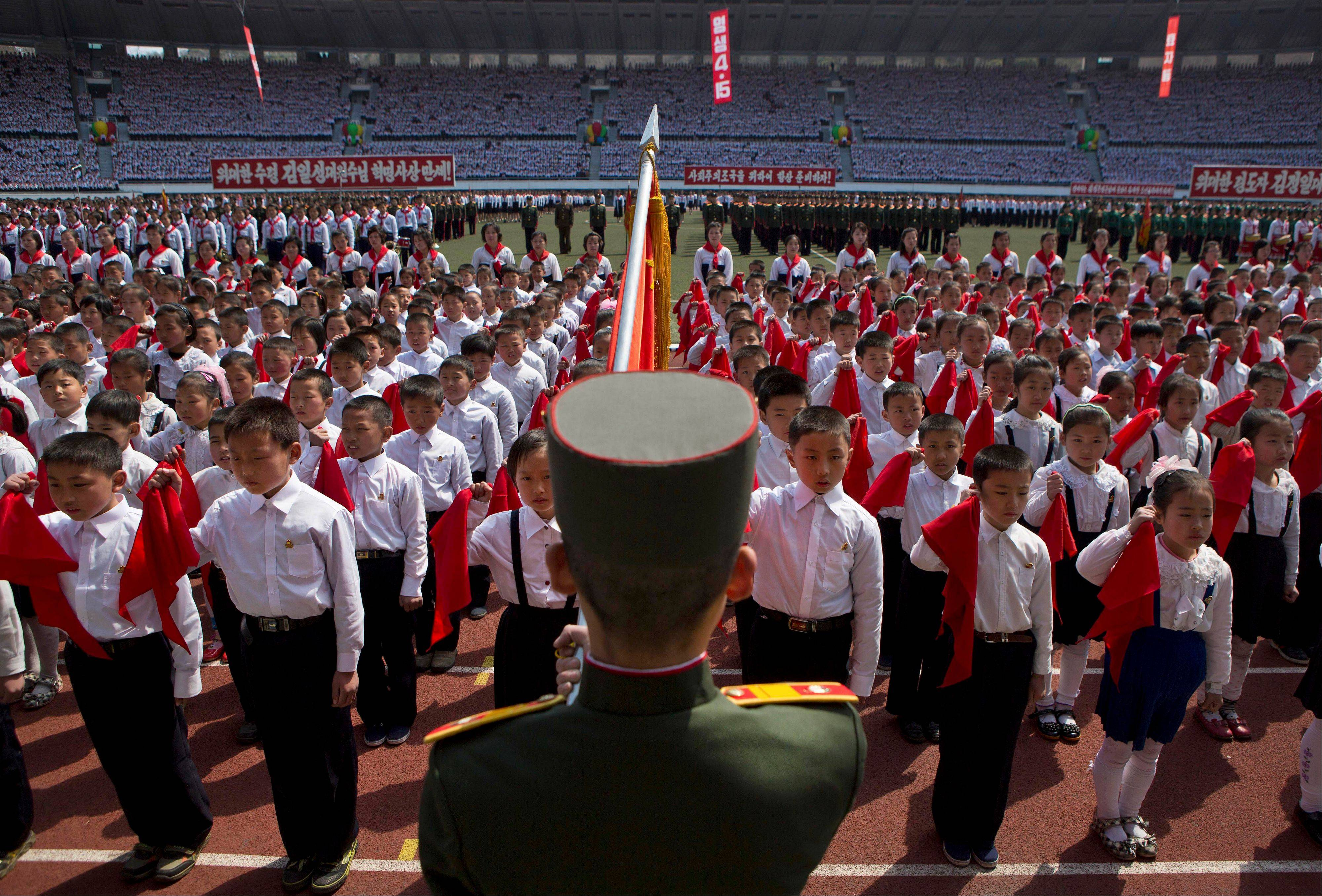 North Korean children hold up red scarves to be tied around their necks during an induction ceremony into the Korean Children�s Union, the first political organization for North Koreans, held at a stadium in Pyongyang on Friday, April 12, 2013.