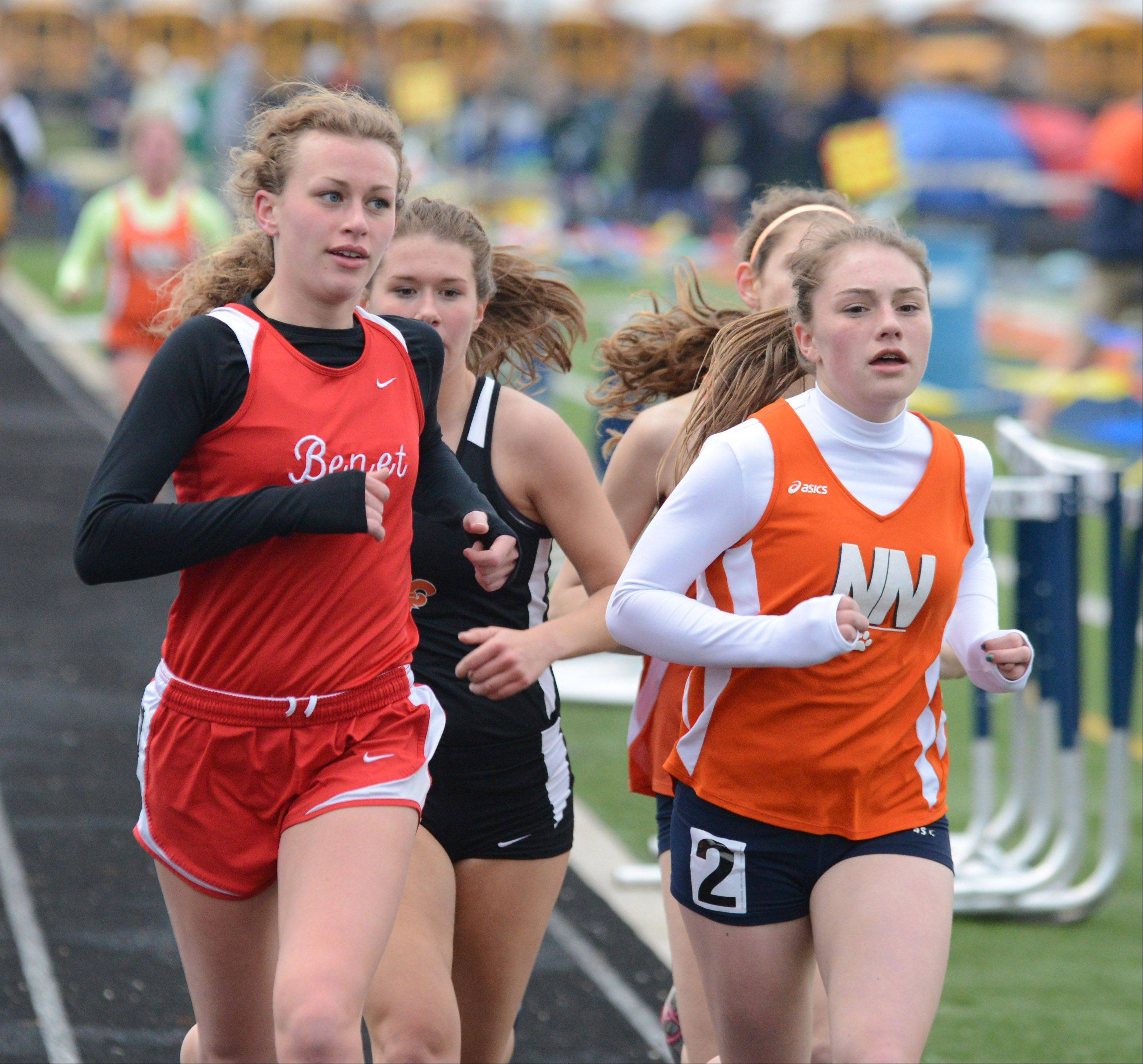 Audrey Blazek of Benet and Emily Hamilton of Napervile North round the corner during the 3,200-meter run at the Gus Scott track meet at Naperville North on Friday.