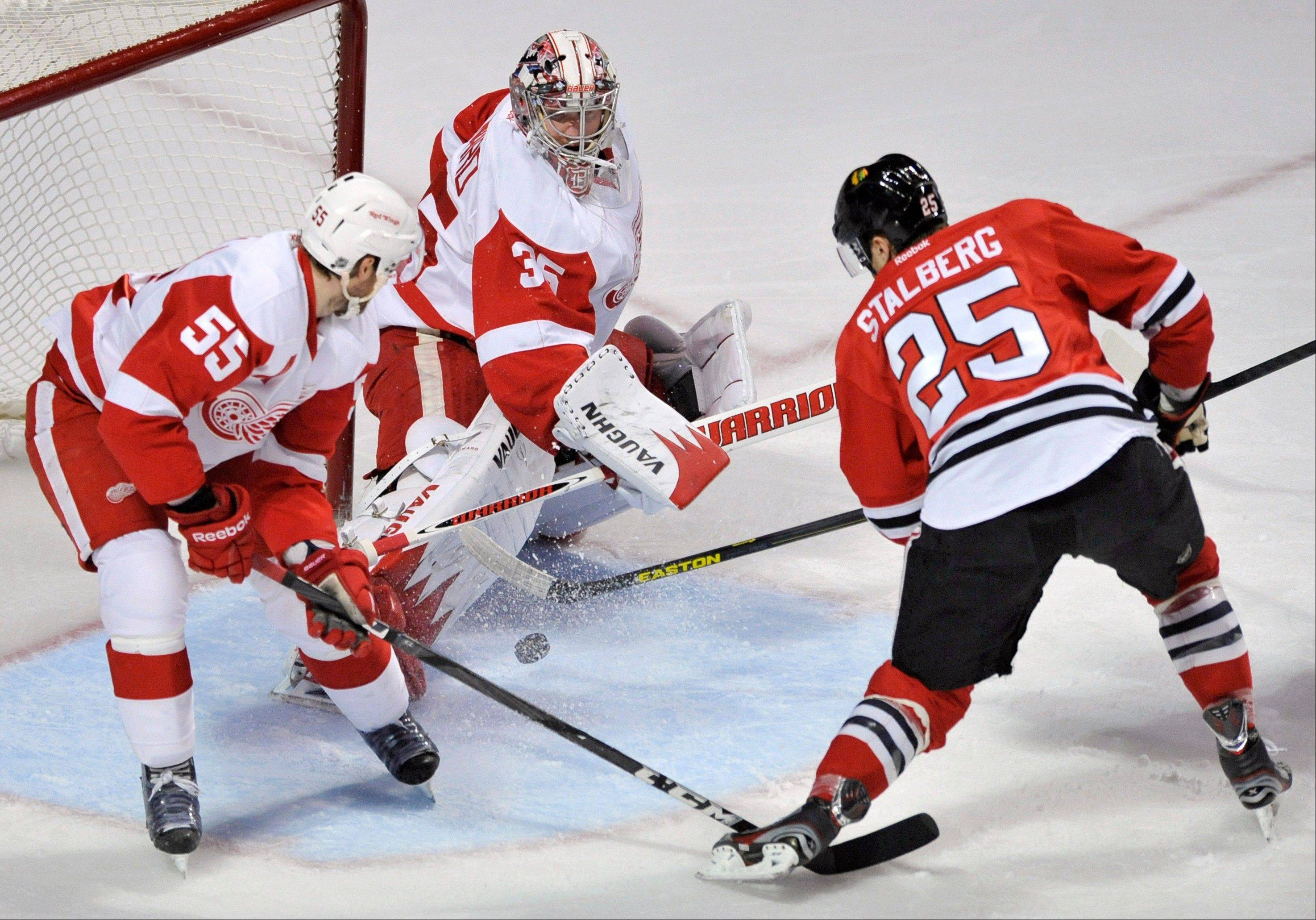Chicago Blackhawks' Viktor Stalberg (25), of Sweden, shoots on-goal against Detroit Red Wings' Niklas Kronwall (55), also of Sweden, and goalie Jimmy Howard during the first period of an NHL hockey game in Chicago, Friday, April 12, 2013. (AP Photo/Paul Beaty)